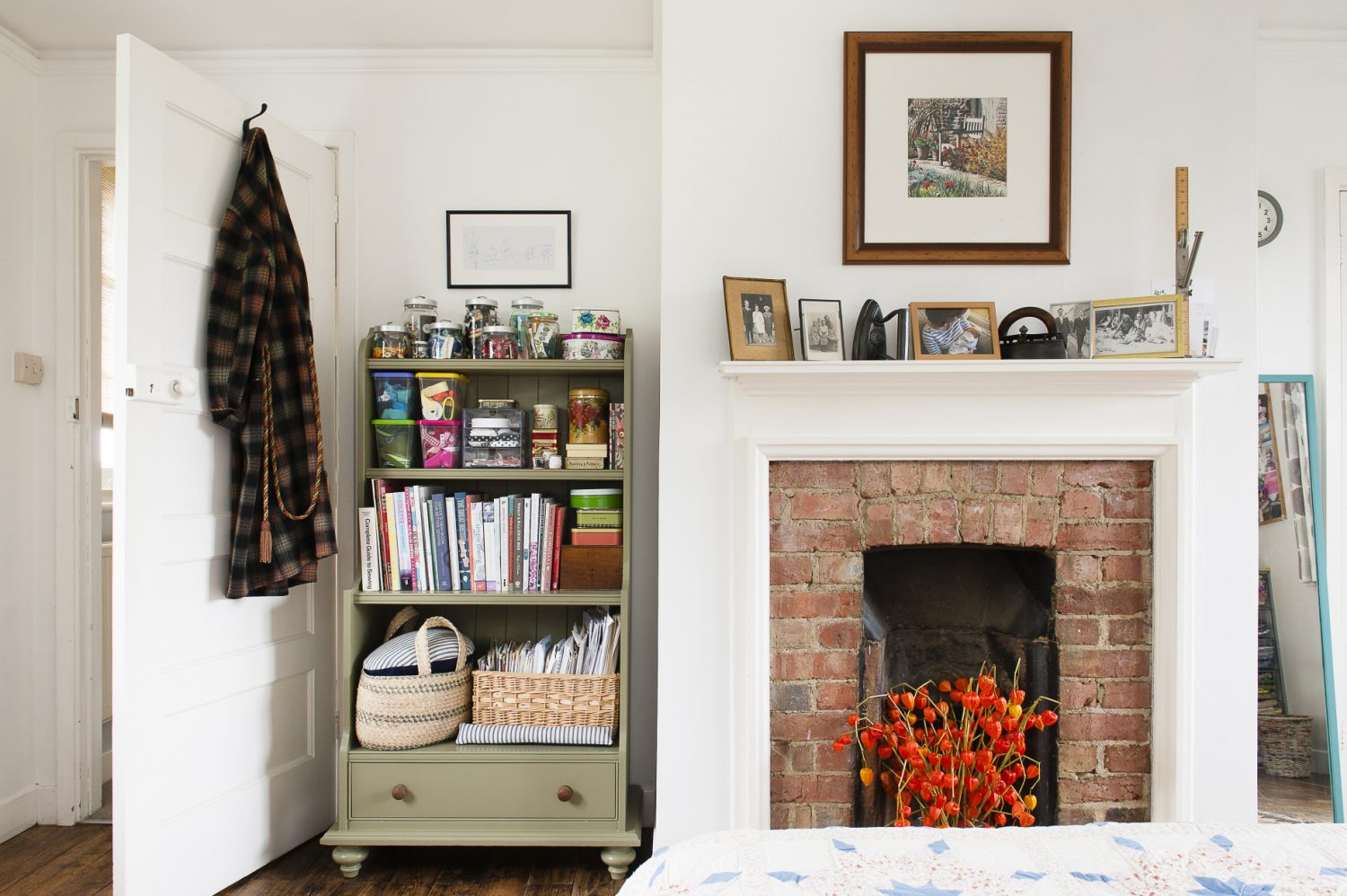 A shelving unit painted in muted, vintage green is used to keep Claire's collection of buttons, ribbon and other sewing items tidy. Claire made the patchwork quilt herself and has filled another unused fireplace with Chinese Lanterns to add some colour and a sense of warmth to the room