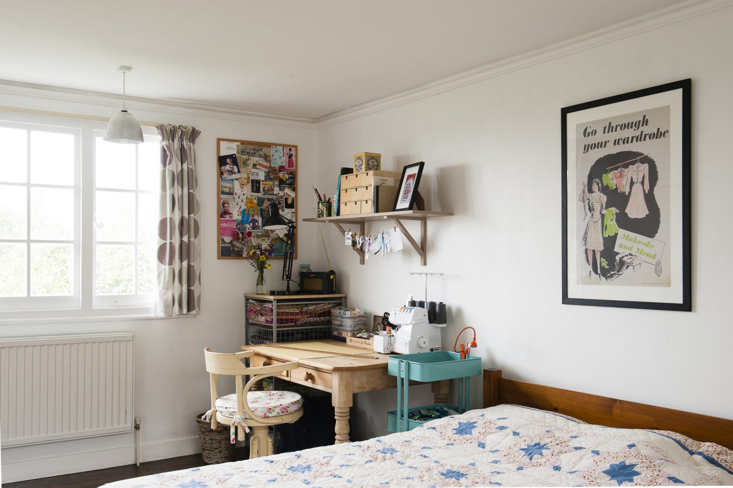 A vintage 'Make do and Mend' poster decorates the spare bedroom, and sits above the homemade quilt and alongside Claire's much-used sewing area