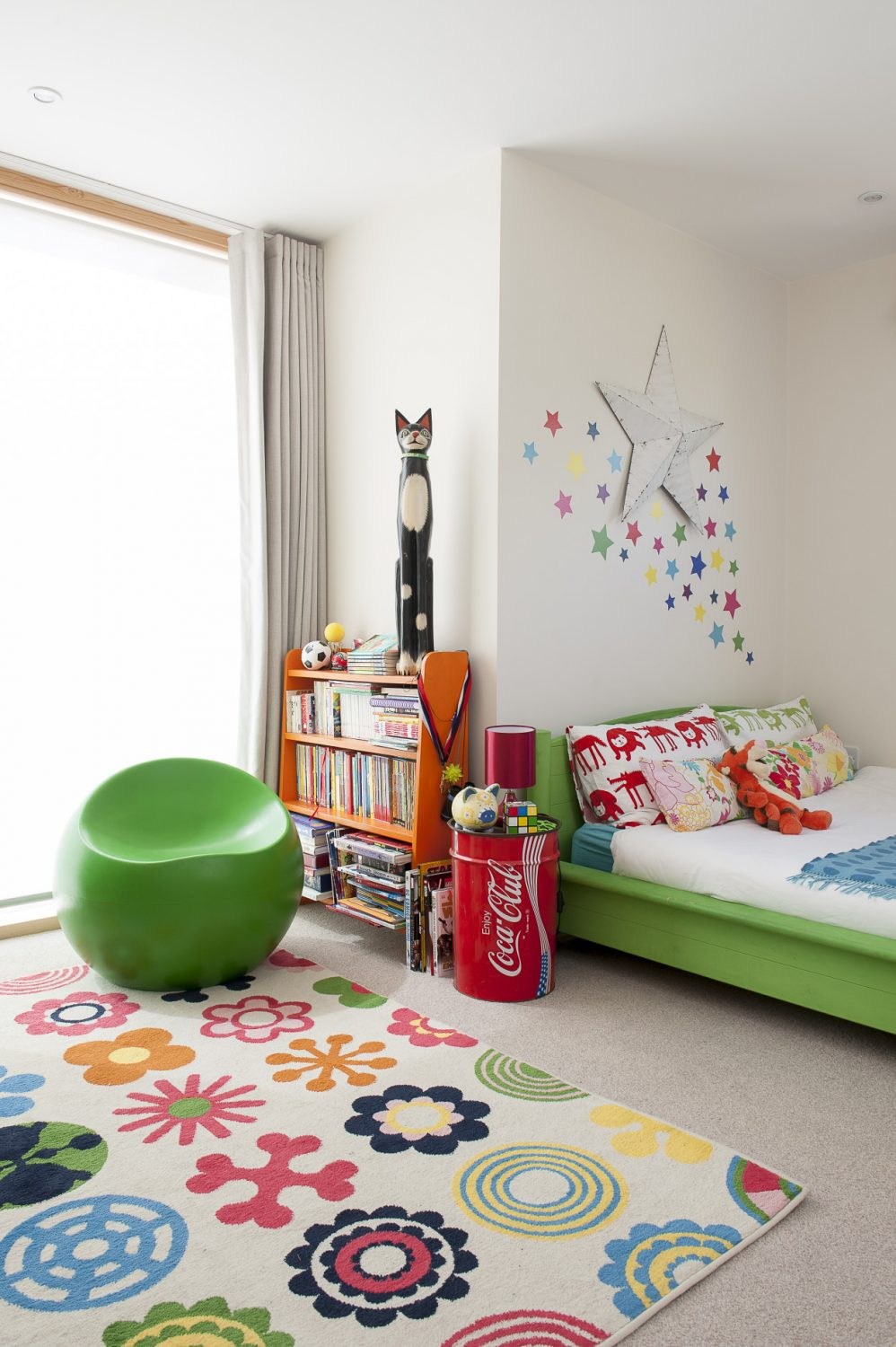 In Jasper's colourfully accessorised room, Jenny has taken an Ikea pine bed and, with the help of Annie Sloan, turned it lime green to match the 60s ball chair. Beside the bed is a Coca Cola drum table and above it a crowd of multi-coloured stars...