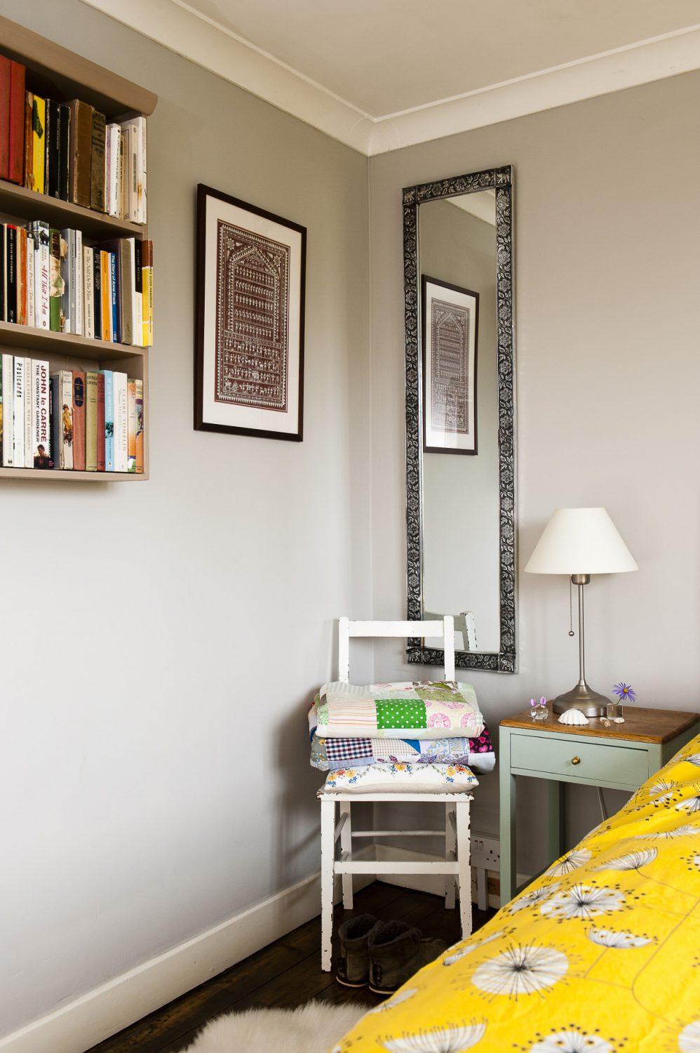 Patterned quilts are folded up on a bedside chair, ready for use when the weather gets cold