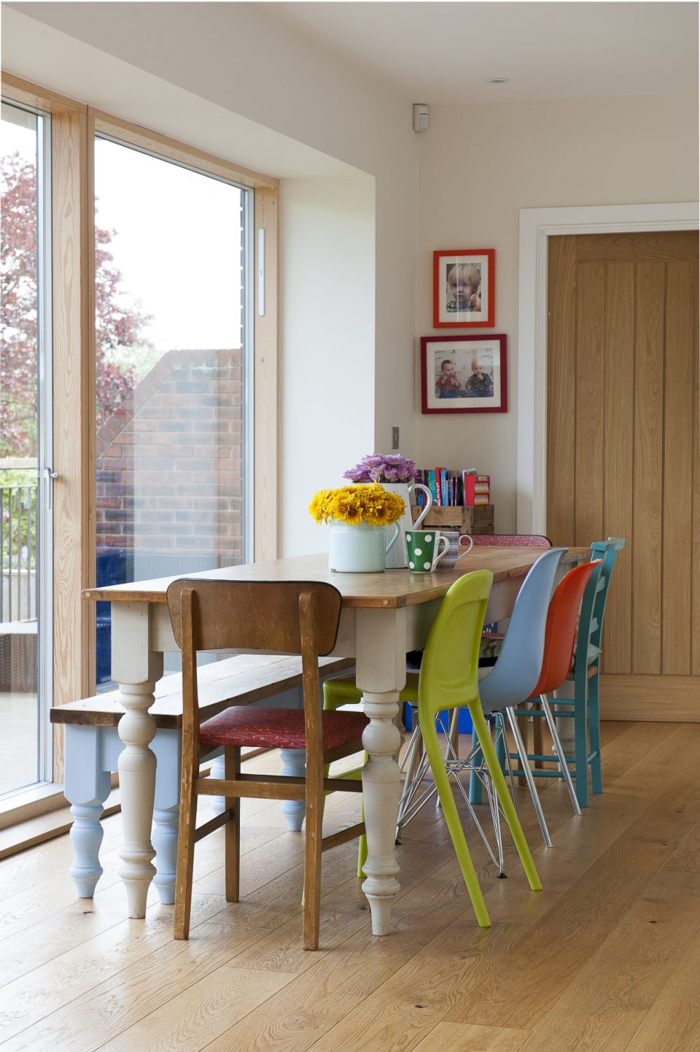 On one side of the pine dining table gather a mix of plastic and metal 1950s/60s and Ikea chairs