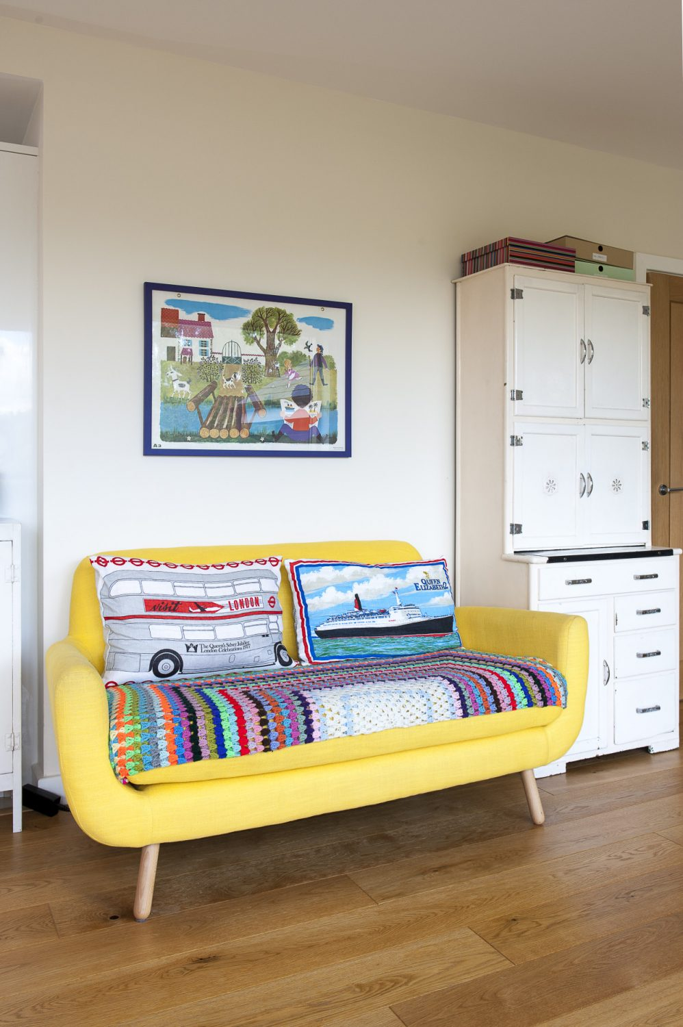 The pretty 60s-style sofa is from Made.com and above it hangs a 1960s French schoolroom poster