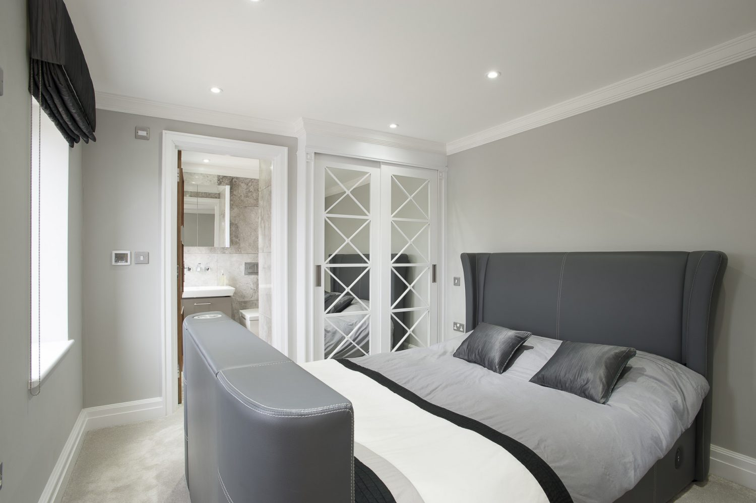 The two guest rooms feature grey leather beds from the feet of which rise flat screen TVs