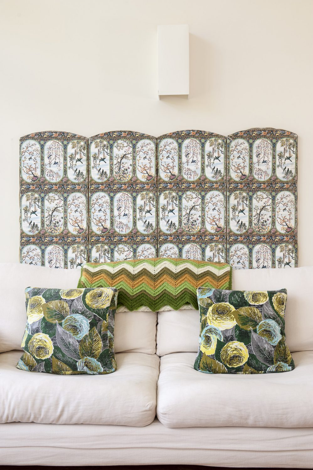 On the wall behind a pale cream sofa is a vintage French screen below which are cushions made by Jenny from bark cloth and old 1960s silk scarves