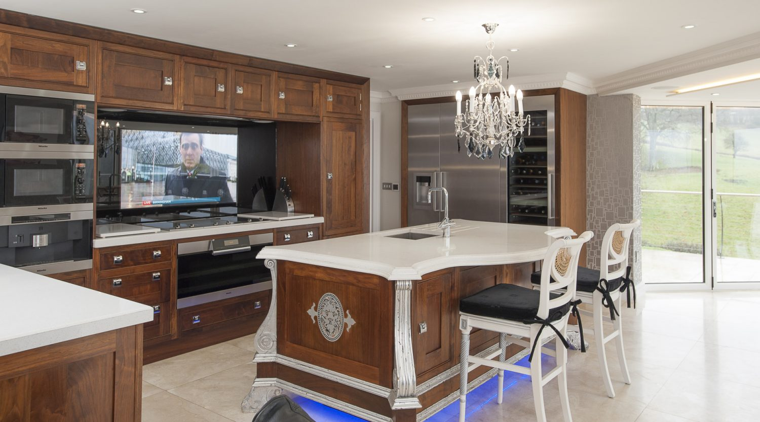 A large TV has been artfully set behind protective glass above the hob so Richard can watch the football while cooking. Also in the kitchen is a full height cabinet that, when opened, reveals more technology than GCHQ – technology that runs the house's state-of-the-art audio-visual systems