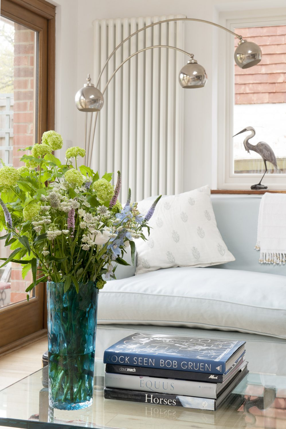 Retro lamps contrast with a vase of pretty cottage garden flowers and an elegant heron sculpture