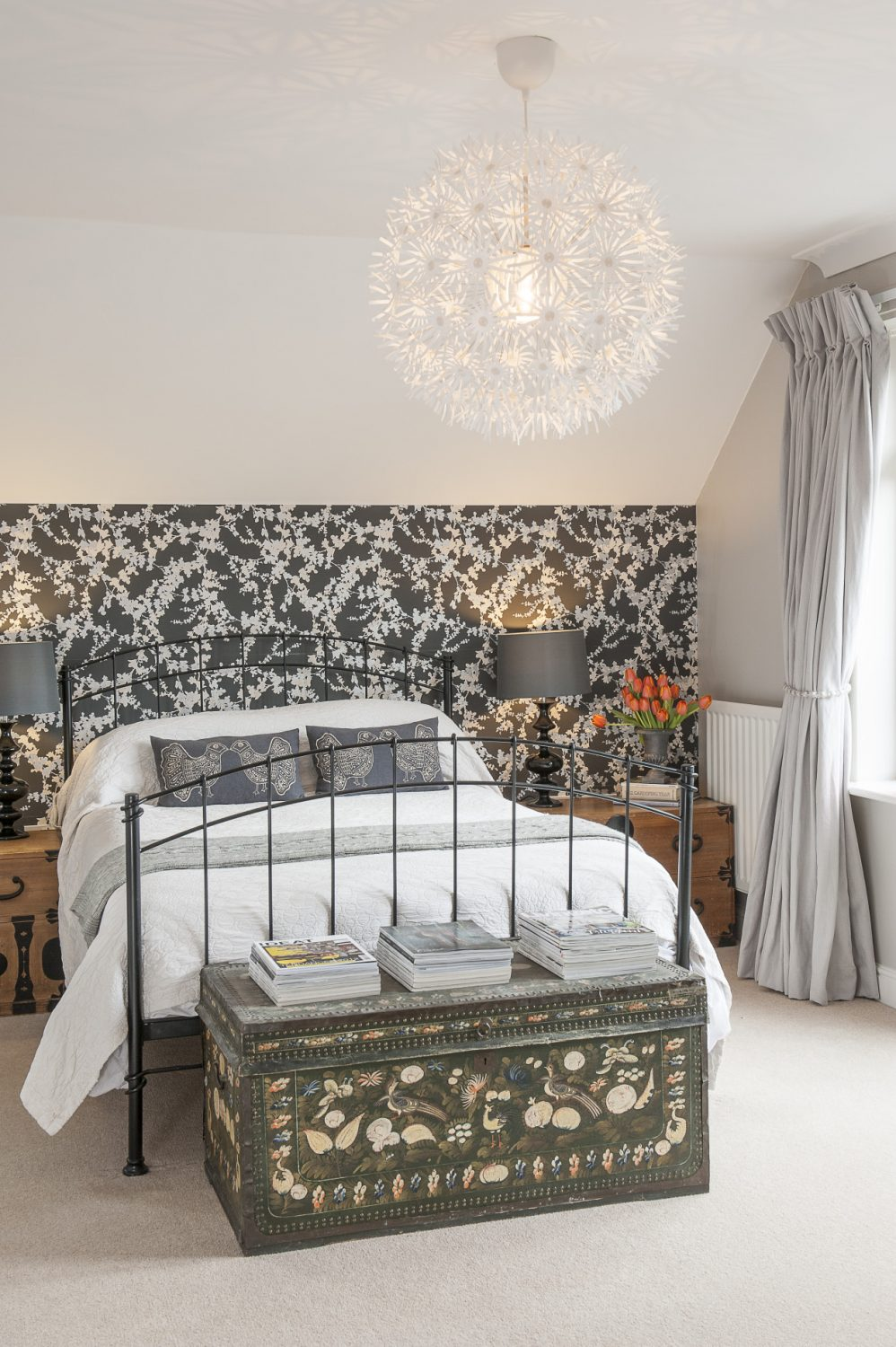 The immaculate guest room and its en suite have been created using products found on the high street – the wallpaper is 'Hawthorn' by Laura Ashley. At the end of the bed is an exquisite painted leather chest that belonged to Phoebe's grandmother