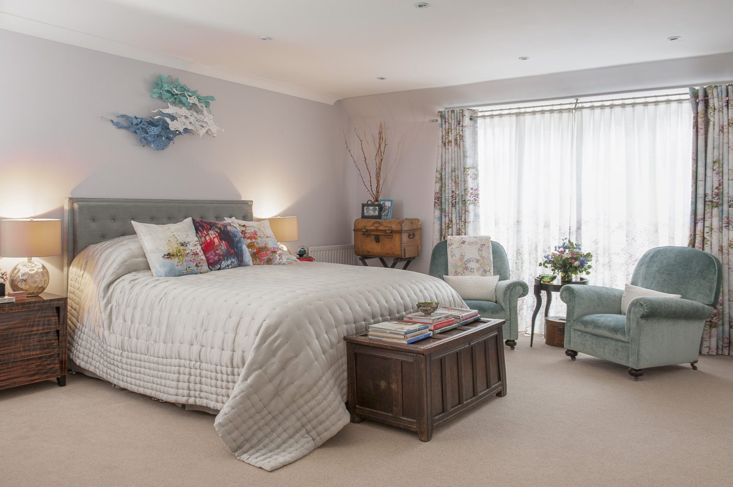 The master bedroom and en suite is a cool and tranquil space. Phoebe found the chairs in the master bedroom on Free-cycle. The wall sculpture above the bed is by Anya Beaumont