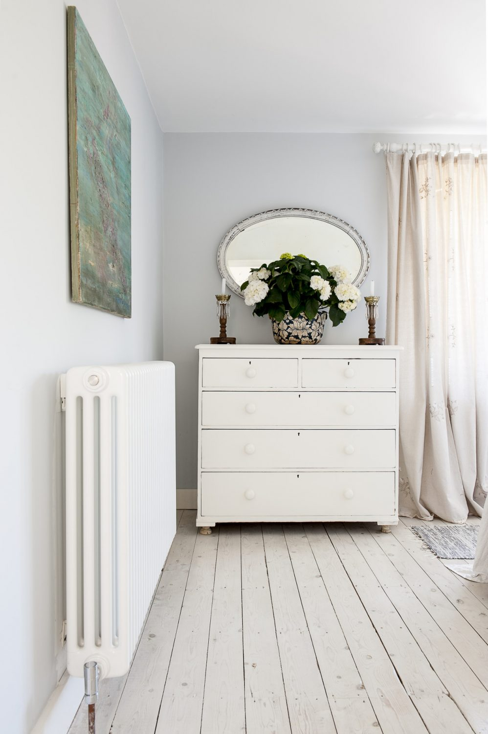 The bedrom is decorated in very simple and restful tones – pale walls and floorboards, curtains made from linen tablecloths found at a Portuguese street market