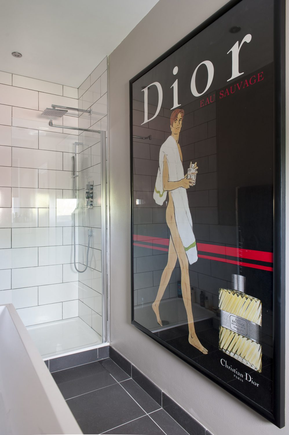 An original Dior poster is all that is needed to decorate the en suite shower room