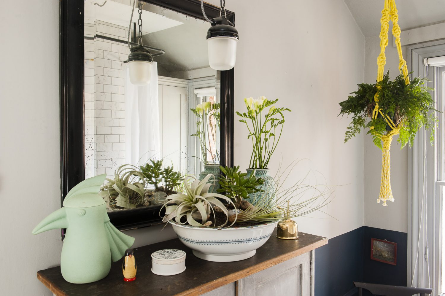 """The bathroom features a bright yellow macrame planter, one of a pair made by James and David. """"We did a course last year. I think the one in the bathroom is probably stronger in terms of the look – that one's David's. I cut the ends too short on mine!"""" says James, modestly."""