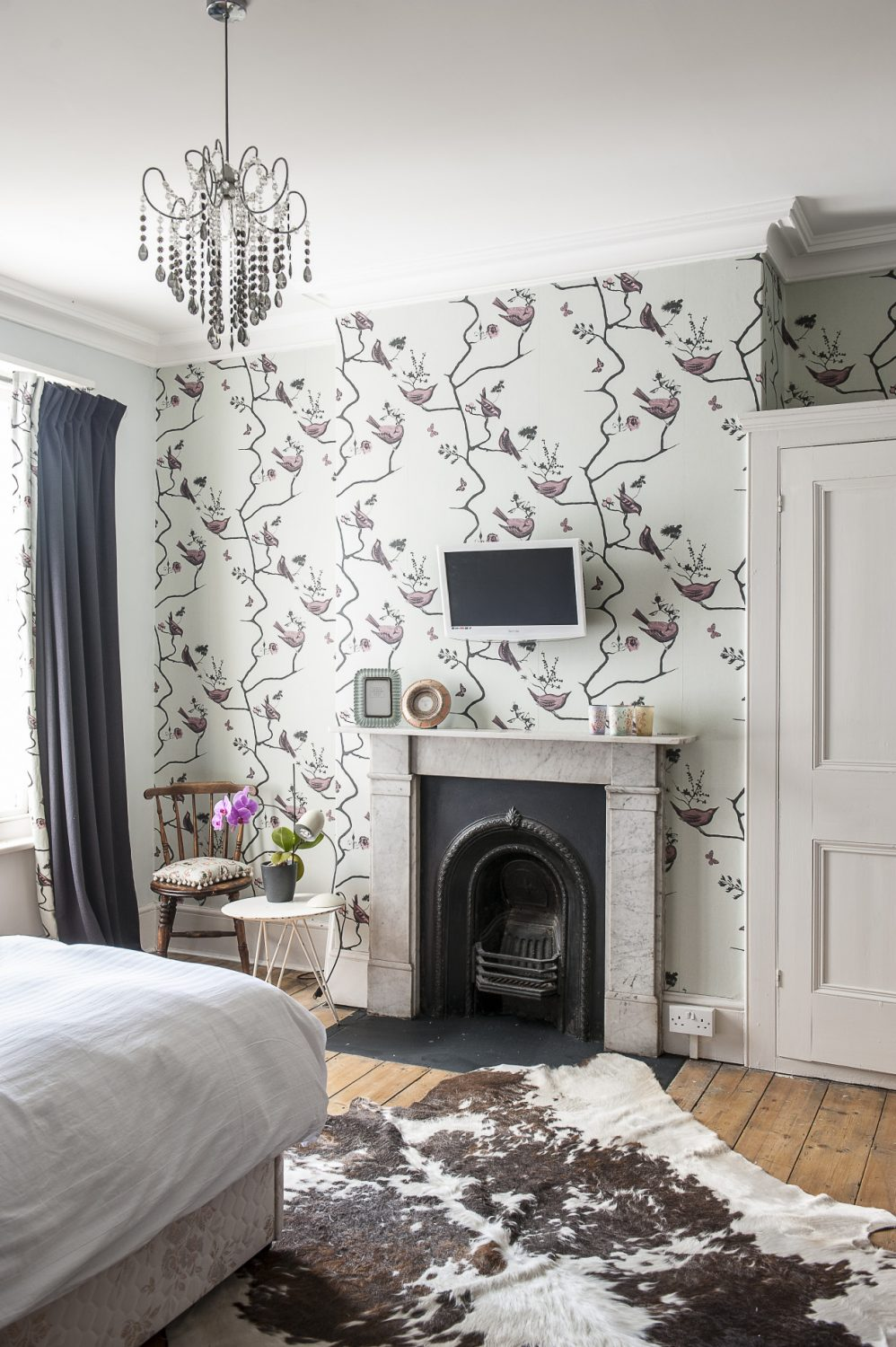 Annette's daughter's room is beautifully tidy. The treatment in this room is simple, but effective. The original fireplace is set off well in a wall covered with 'Pavilion Birds' wallpaper by St. Leonards designer Louise Body