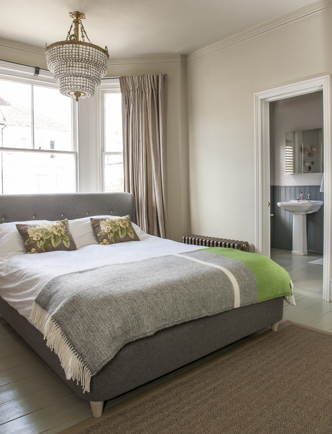 In the master bedroom at the front of the house, the bed is tucked into the bay of the window, maximising the space available and allowing space for the en suite bathroom