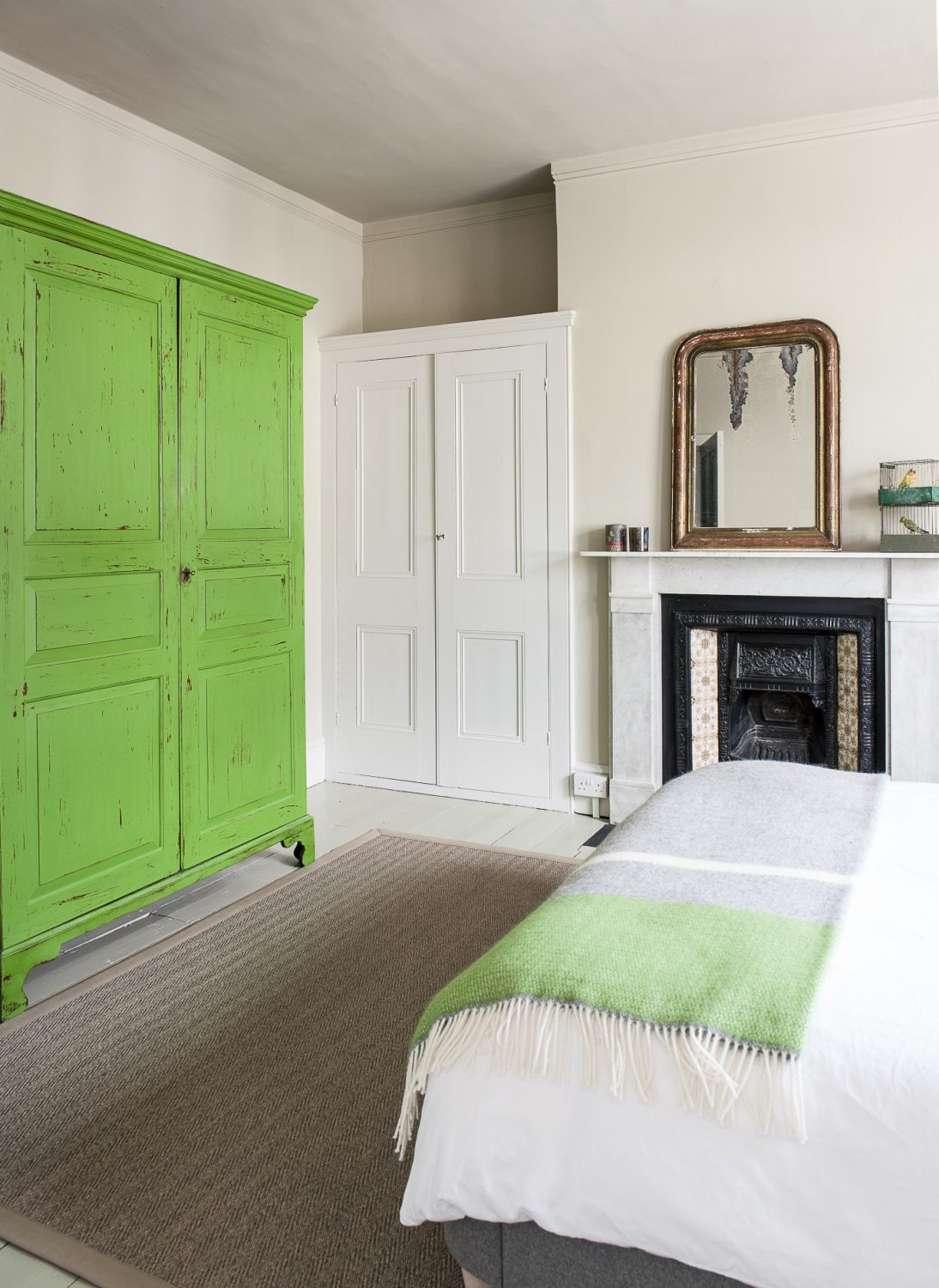 "The scheme in this room is dominated by a large wardrobe – a cloak cupboard from the House of Lords that was given to Annette by an aunt. Annette has painted it bright green. ""I was going to paint the whole room that colour but I chickened out and just kept it to the cupboard."""