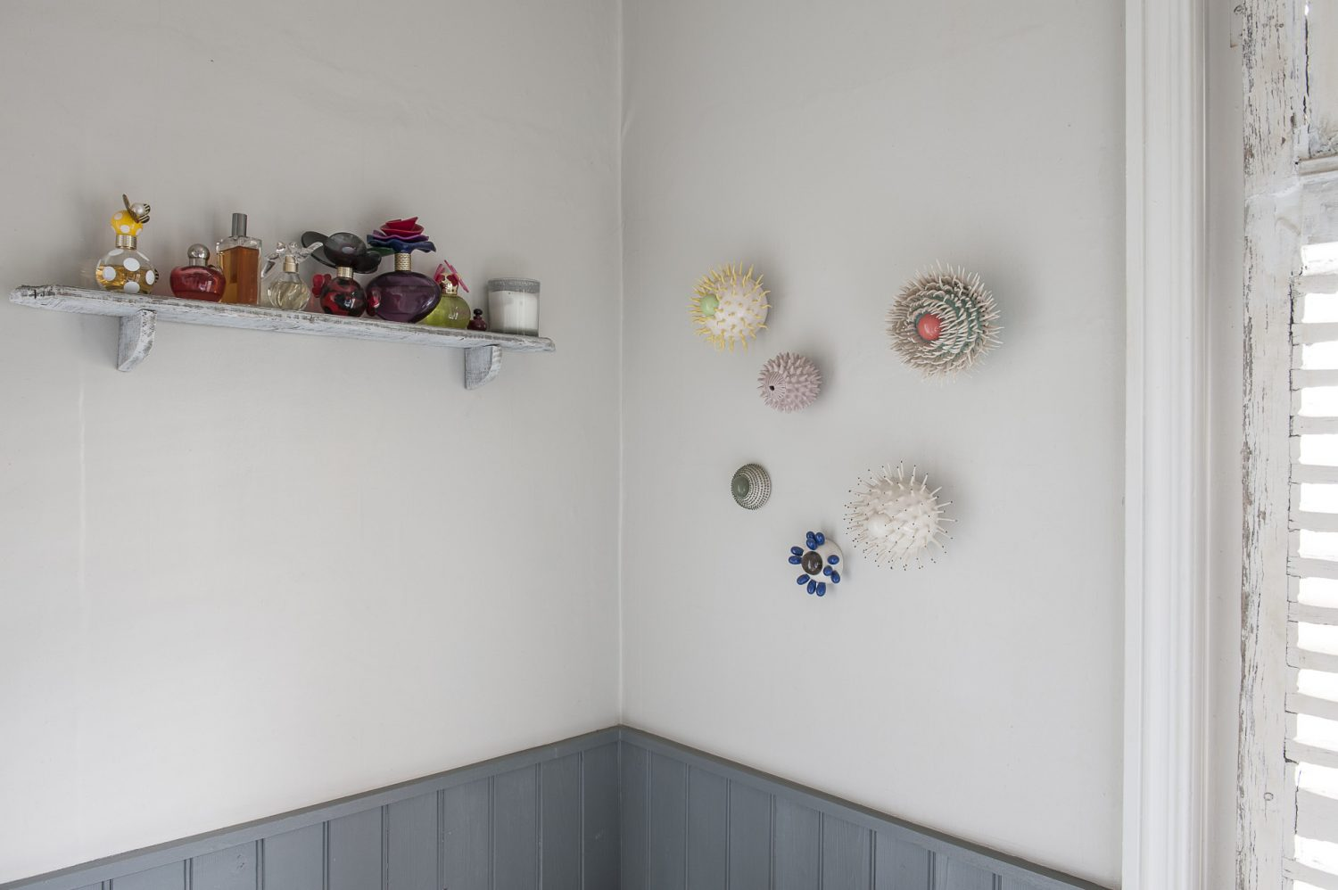 A grouping of spiky ceramic sculptures, reminiscent of sea anemones, from Myung Nam An are mounted on one wall
