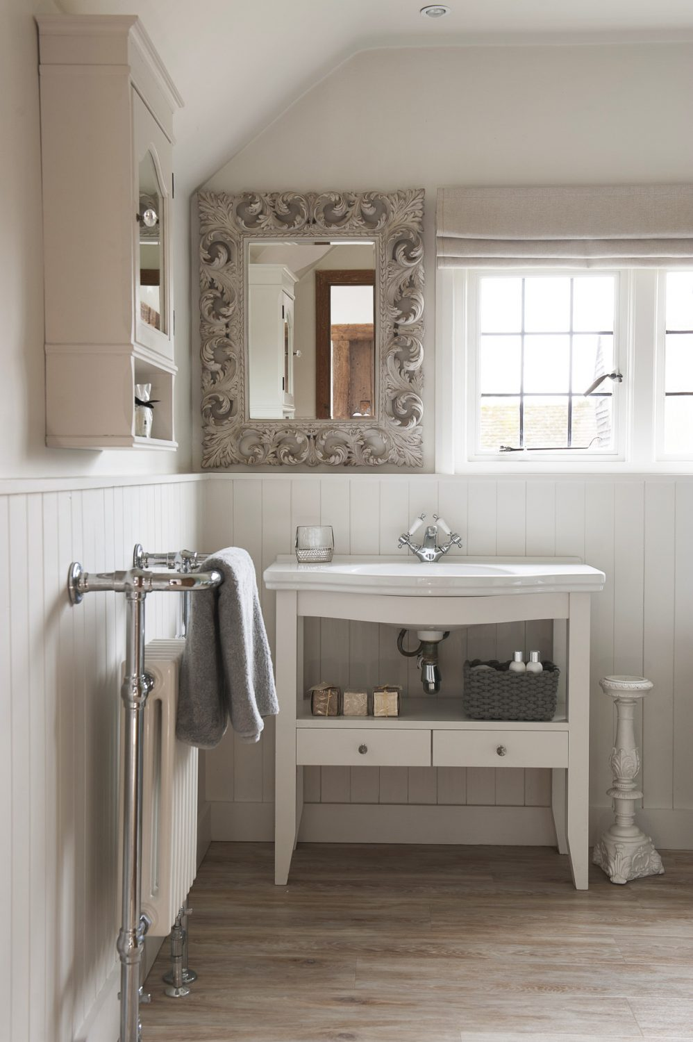 An ornate mirror is a feature in the classic, welcoming bathroom, where tongue-and-groove panelling adds a country cottage feel alongside the painted wood sink unit