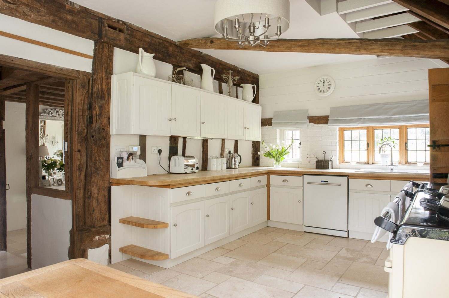 The modern, clean-white kitchen contrasts with the rustic beams and period features of this Wealden farmhouse
