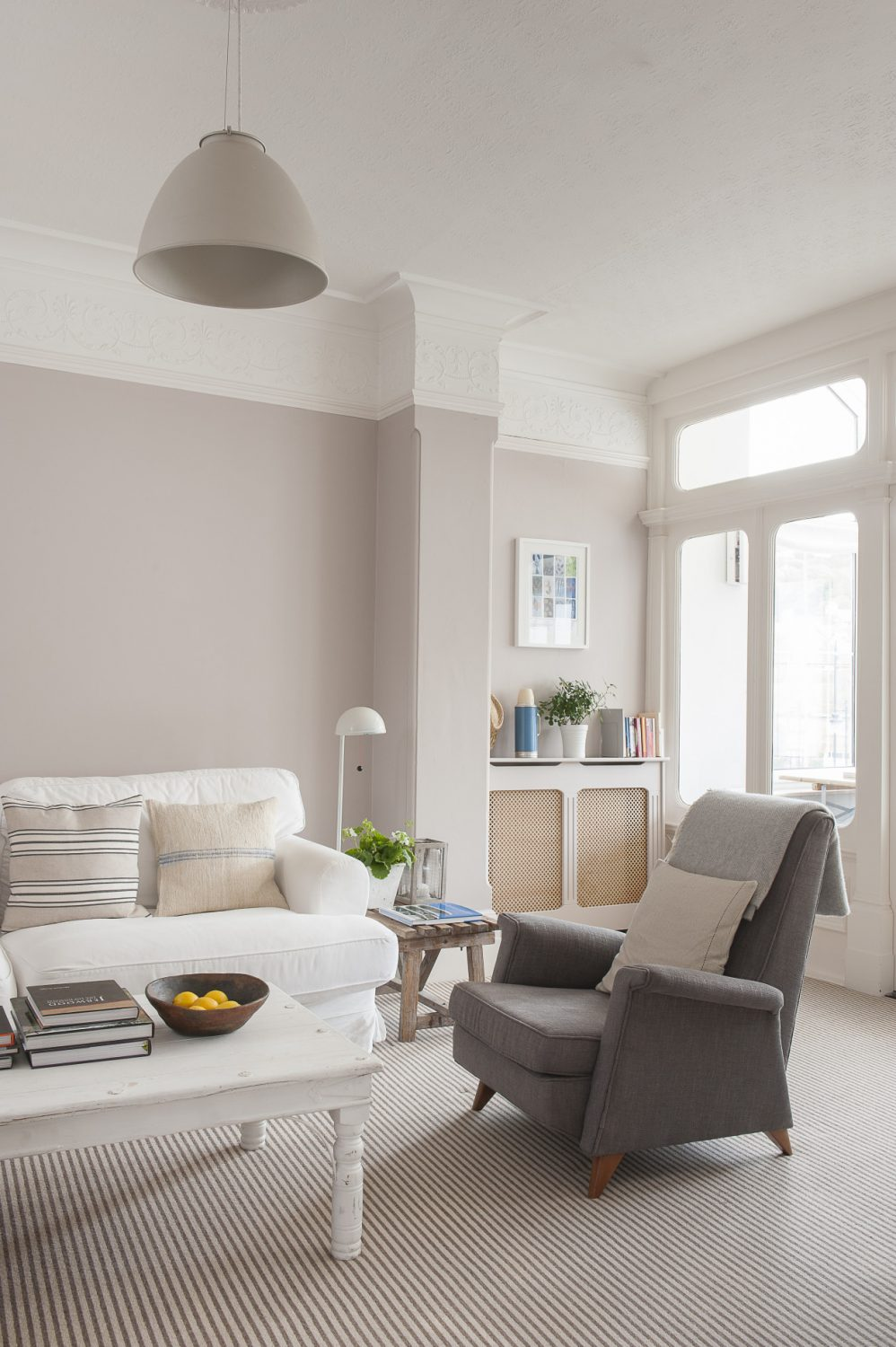 A white sofa and two Parker Knoll chairs flank a chunky white-painted coffee table topped with art books