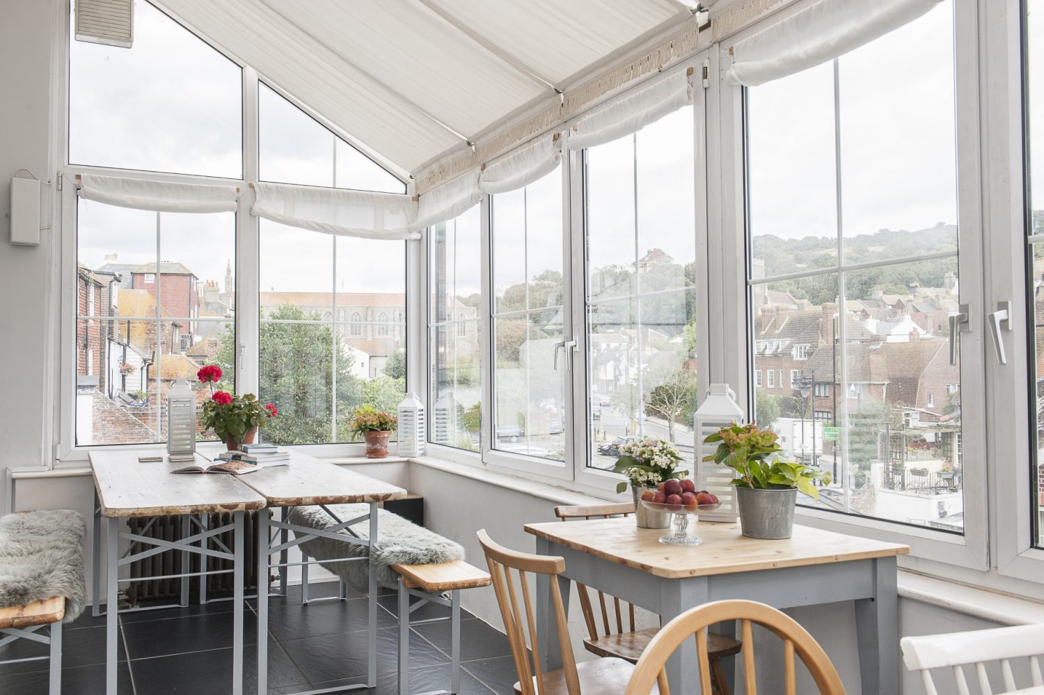 Two steel-framed trestle tables and benches draped with sheepskins provide cosy seating in the breakfast room