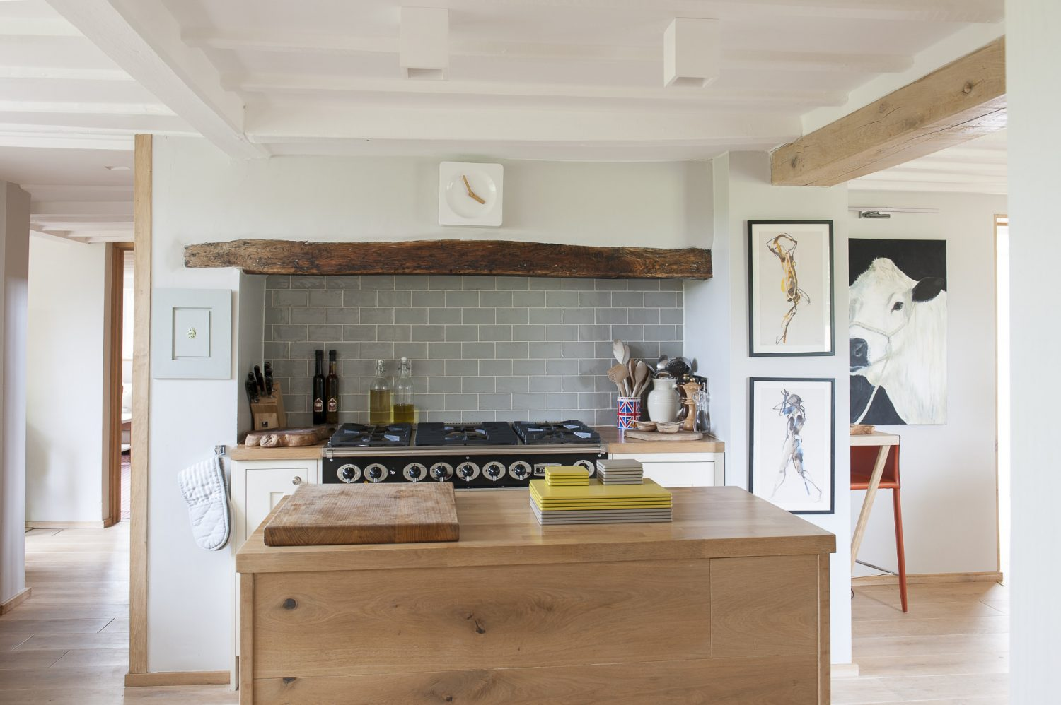 The light-filled kitchen once had an unreliable old Aga at its heart – since replaced by a range cooker. The kitchen units are by Howdens and are complemented by light, machined-oak floorboards. Martine and Andrew are big fans of the artist Bella Pieroni whose pictures hang to the right of the cooker