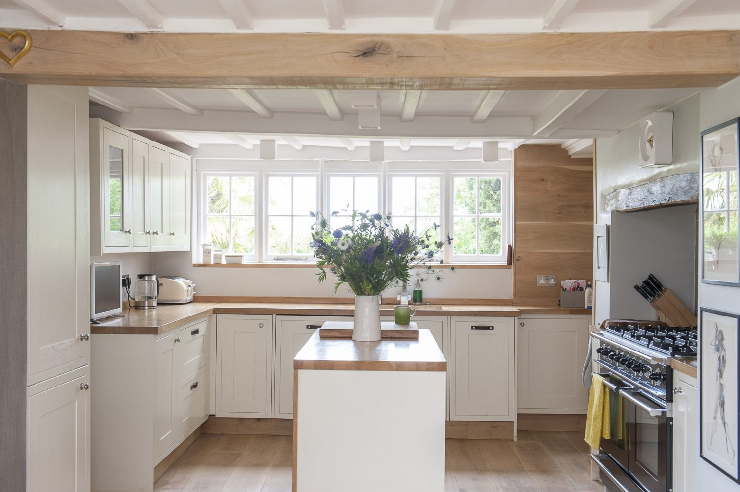 Cream-painted units and pale oak worksurfaces reflect the light