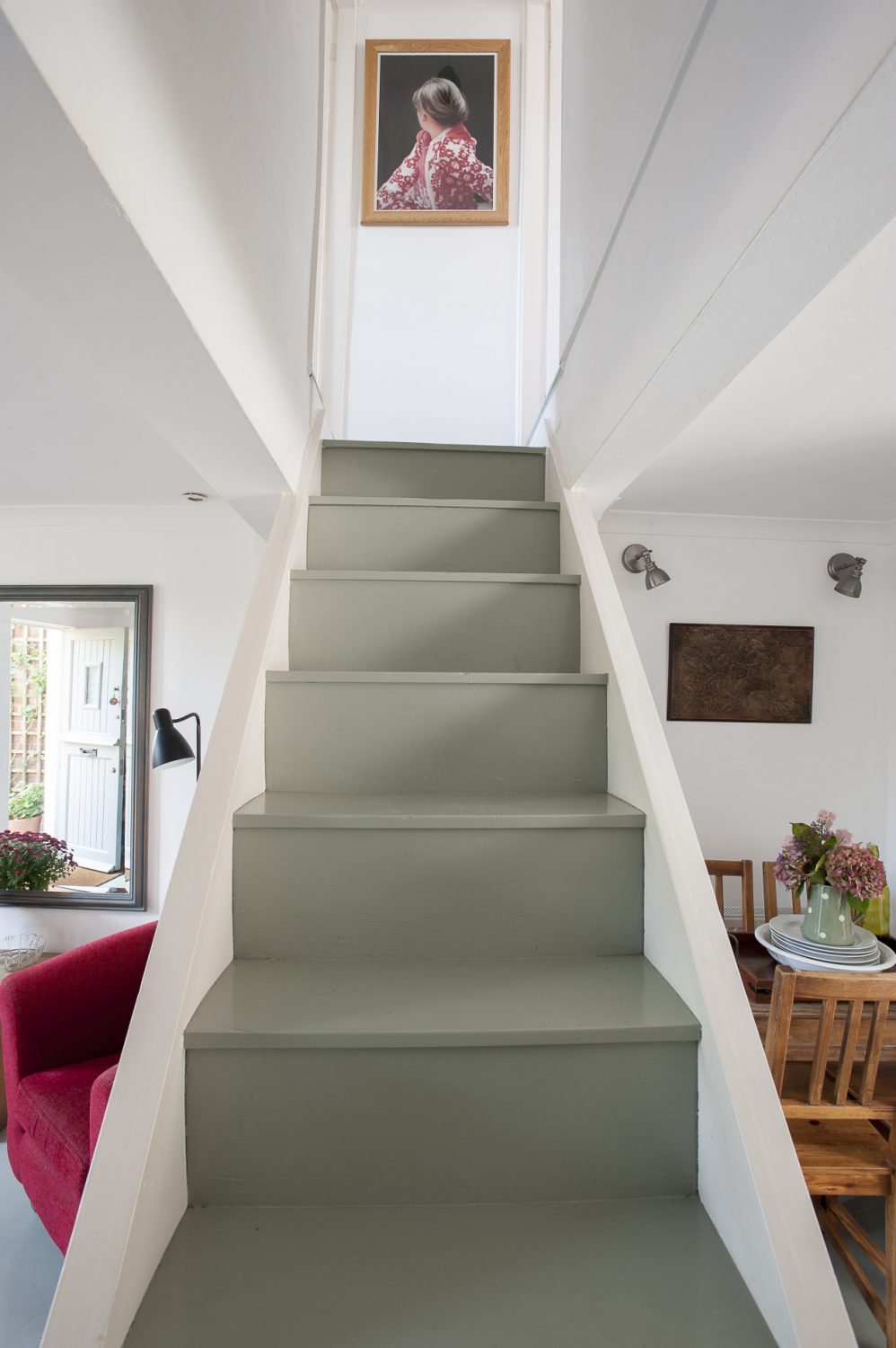 The staircase in the centre of the living room leads to the two upstairs bedrooms