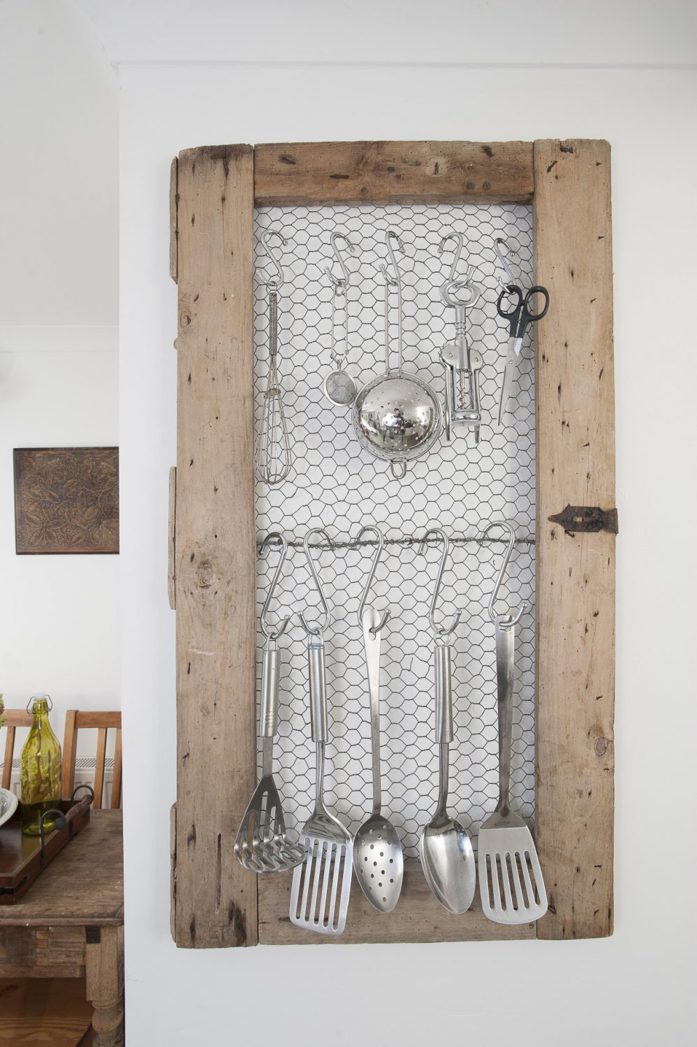 On the wall is a clever French find that has allowed Linda to indulge in her passion of displaying every-day objects: an old pair of cupboard doors backed with chicken wire