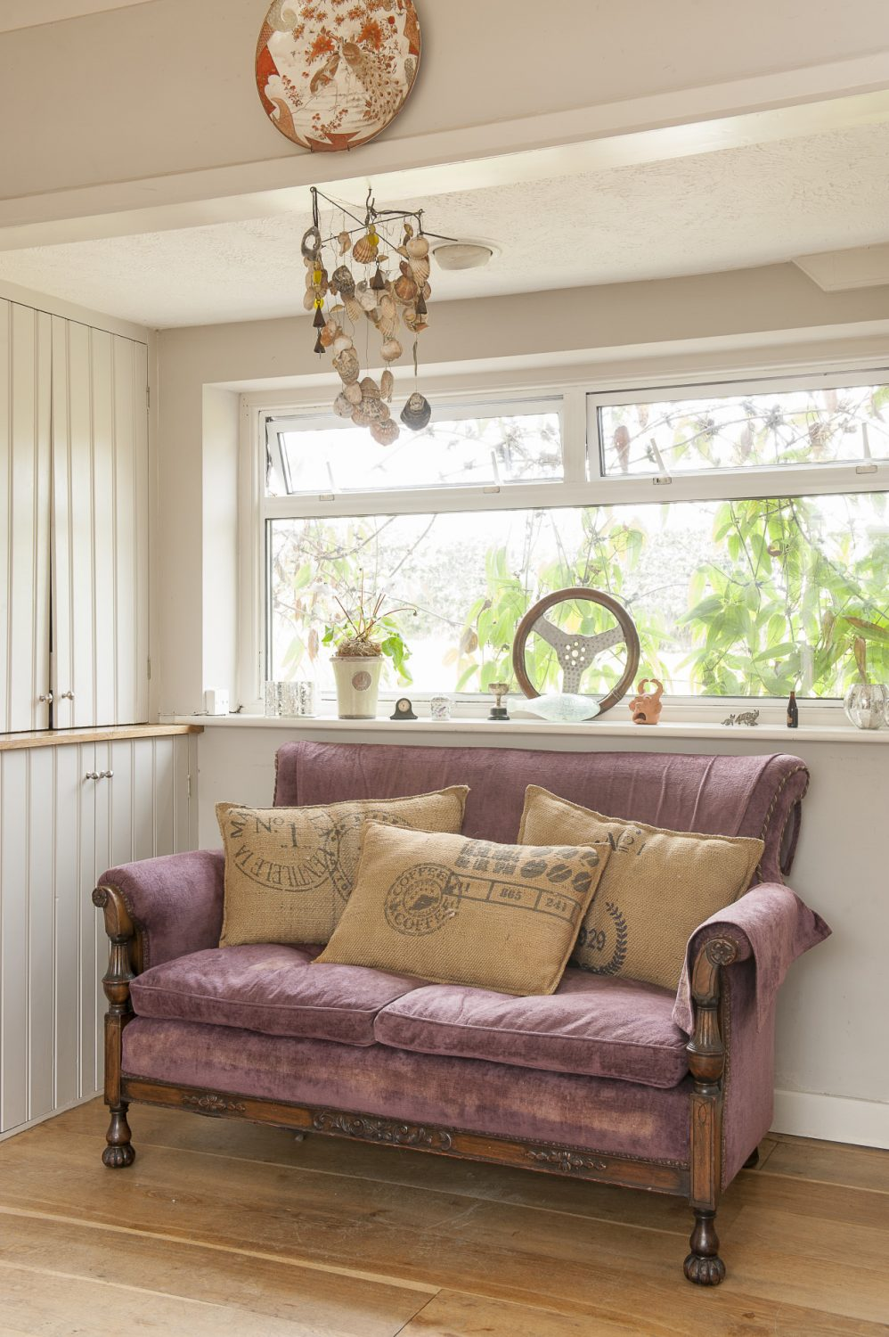 A velvet sofa tucks neatly into an alcove by the kitchen window