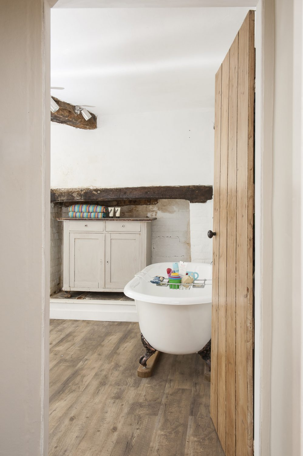 A painted cabinet nestles into the original fireplace in the family bathroom