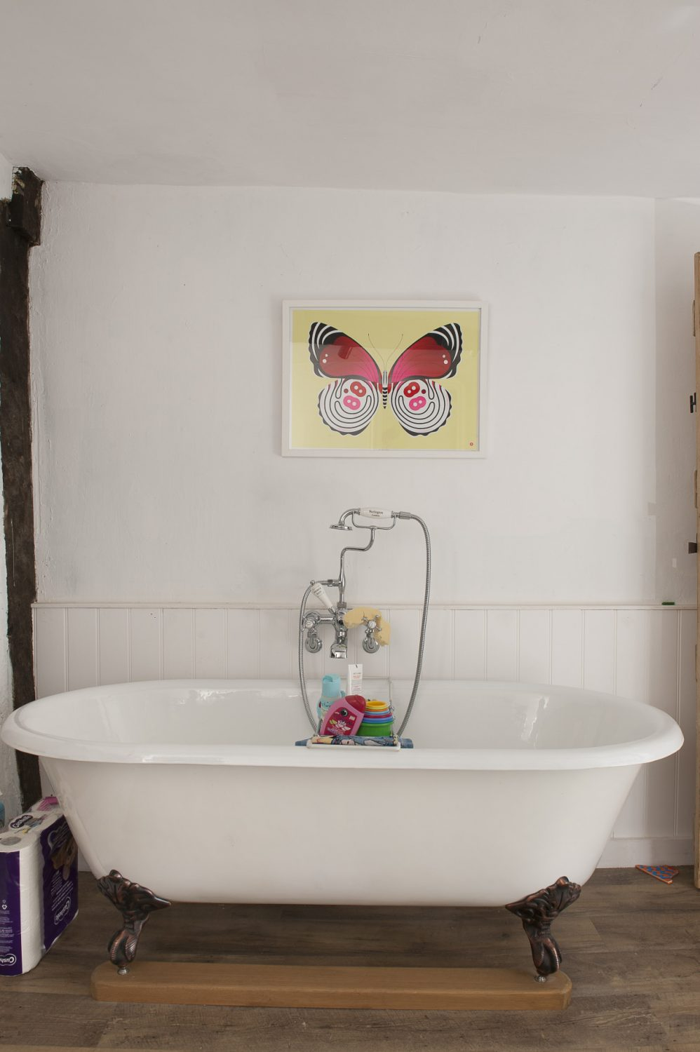 the butterfly print above the bath adds a playful and colourful touch to the otherwise pale interior