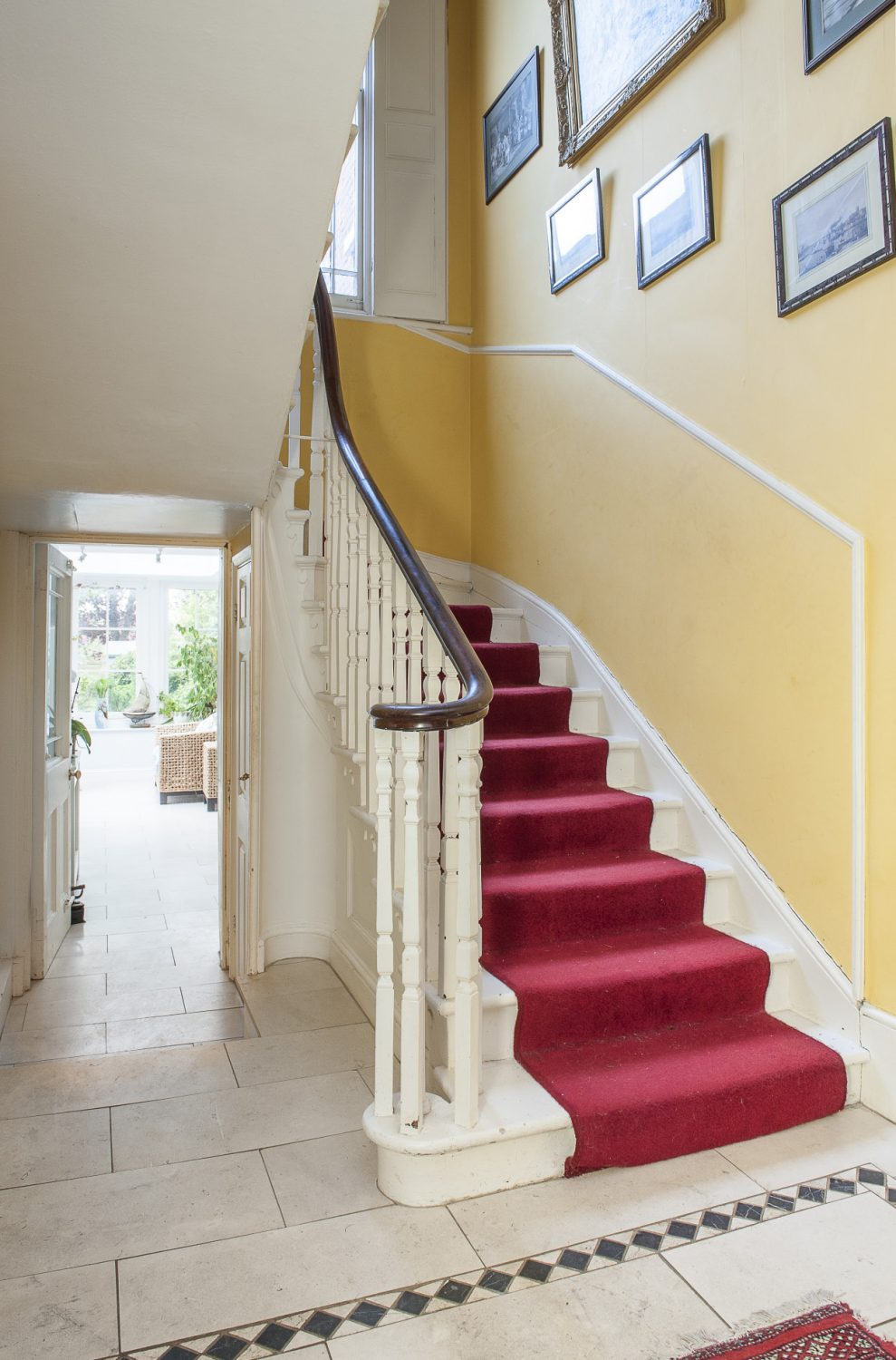 The sunny yellow of the hallway continues up to the soaring ceiling of the landing
