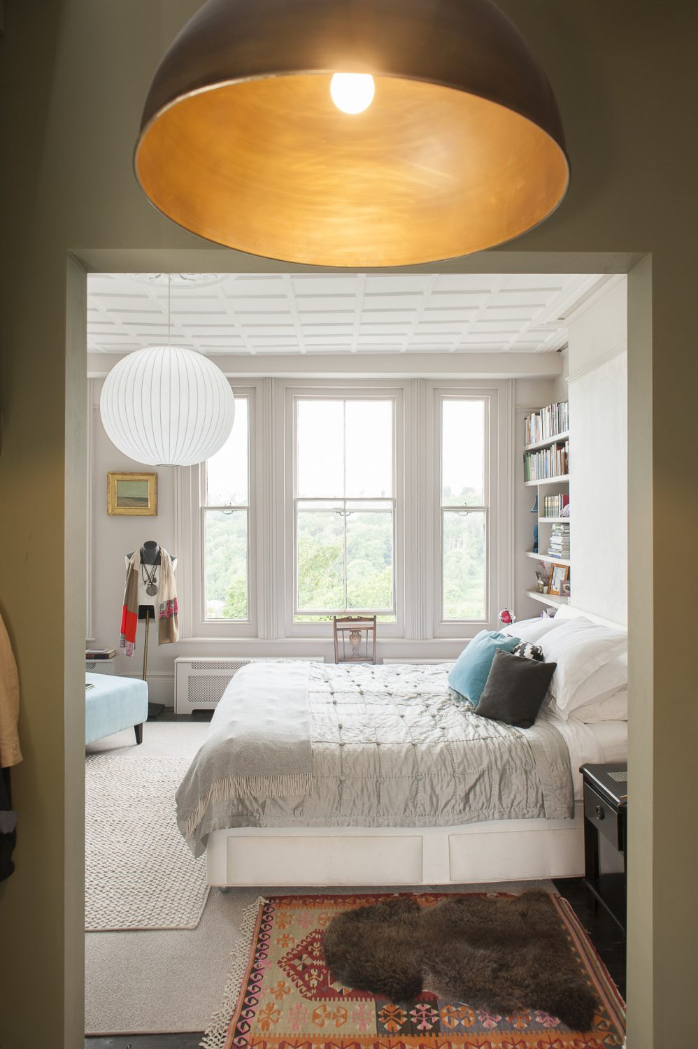 The pale grey bedroom is linked to the bathroom by an olive green dressing room. The striking copper light fitting is by Jim Lawrence. The seascape on the far wall is by Anne Packard. The white and steel pendant light is one of a number of George Nelson classic lights throughout the house