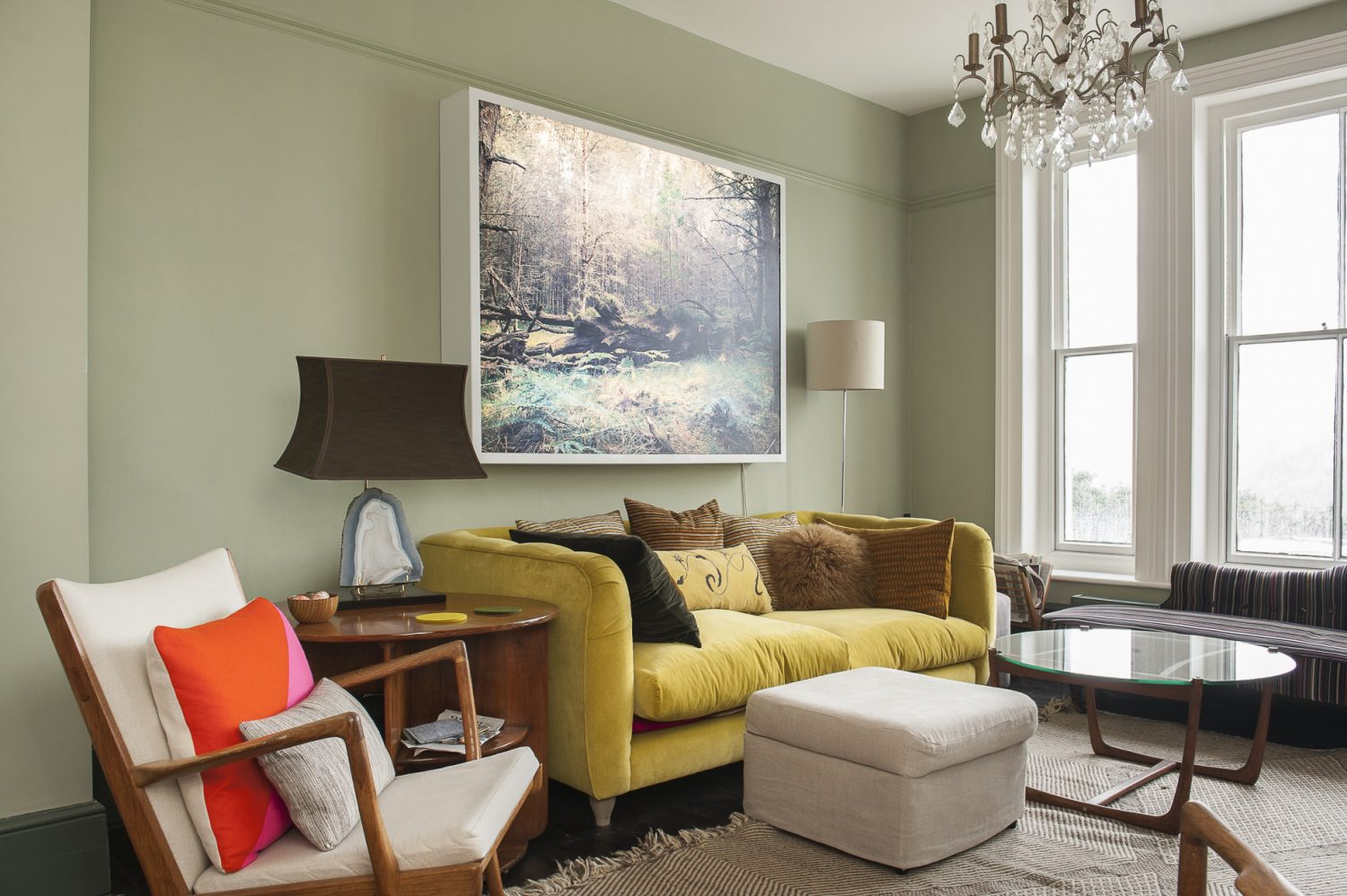 The sitting room looks out over Hastings Old Town to the sea. The sofa - in Ginny's beloved yellow - is by Loaf and the artwork above it is a lightbox installation of a woodland scene by Dalziel + Scullion