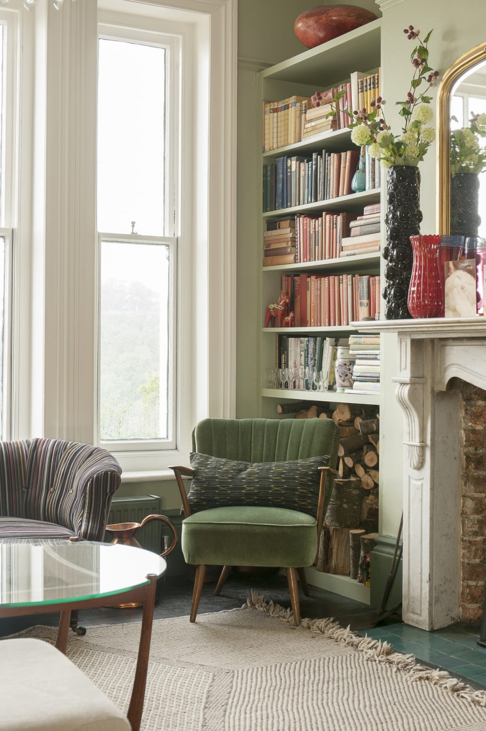 The marble fireplace is original to the house, with bookshelves on either side a hint to Ginny's occupation as a writer, with logs stored beneath. The green chair is from a junk shop in Hastings Old Town. Fresh flowers - and Abigail Ahern's faux wildflowers - are displayed in Ginny's collection of vases sourced over the years from Paris flea markets, Shoreditch junk shops and vintage Murano from Venice back streets
