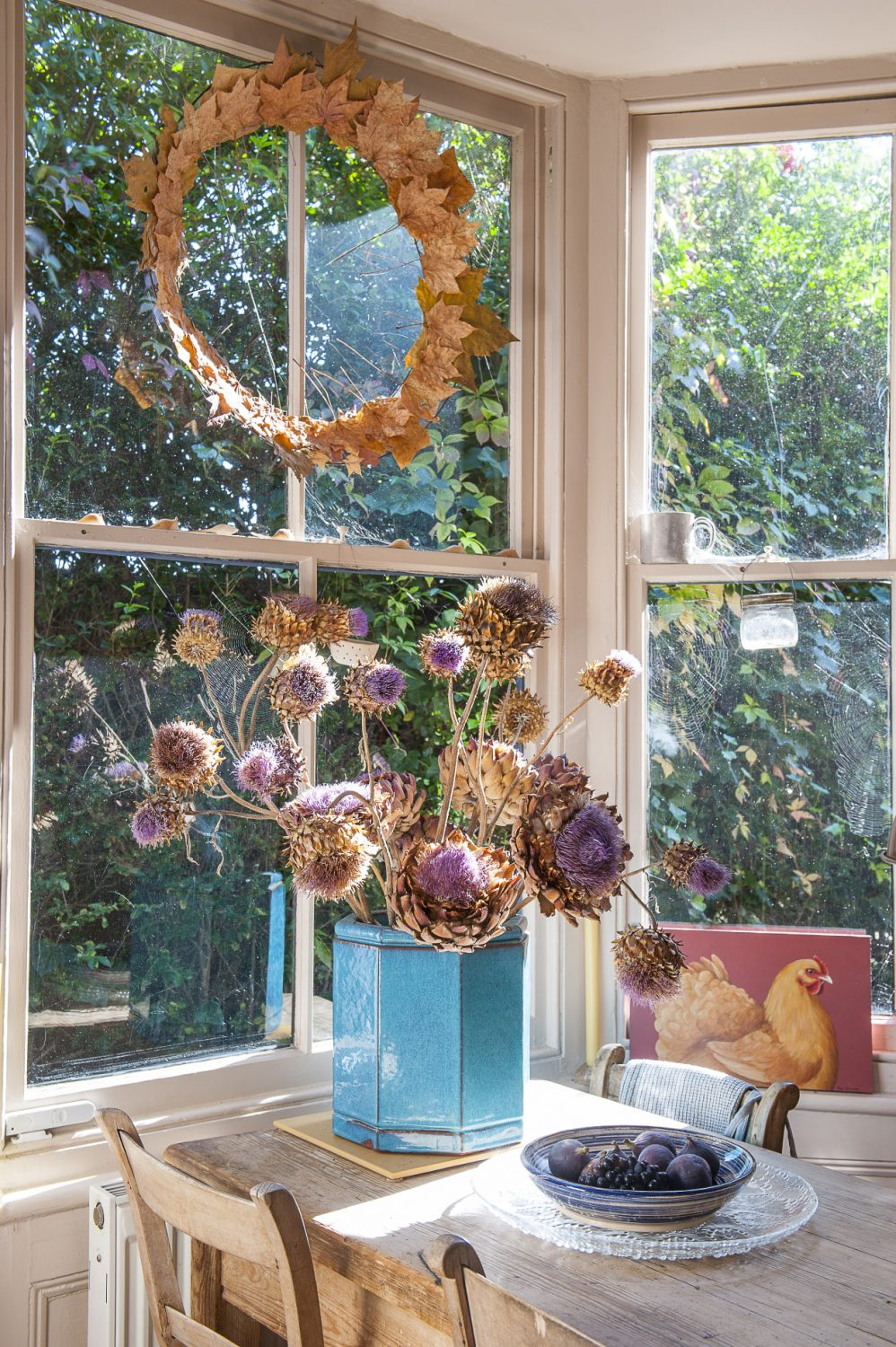 A vase that belonged to Francine's grandmother is the perfect container for cardoon and artichoke heads. Overhead is a wreath made from leaves that were pressed between newspaper placed under a doormat