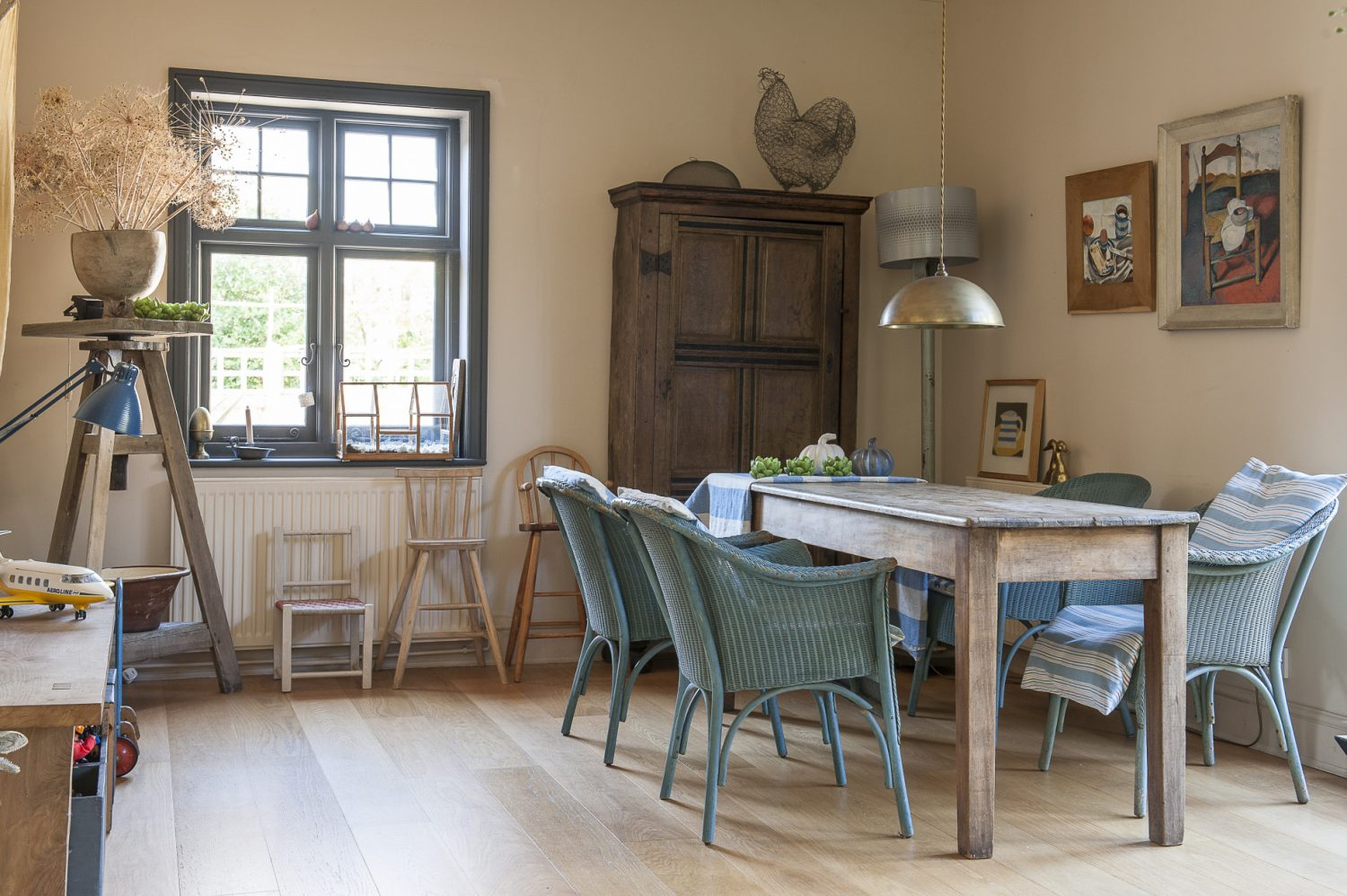 Lloyd Loom chairs from Francine's Suffolk home are a comfortable and informal addition to the refectory table, while the 17th-century Flemish wardrobe acts as a perch for a wire sculpture of one of Francine's Buff Orpington hens, by the Norfolk sculptor Jenny Goater