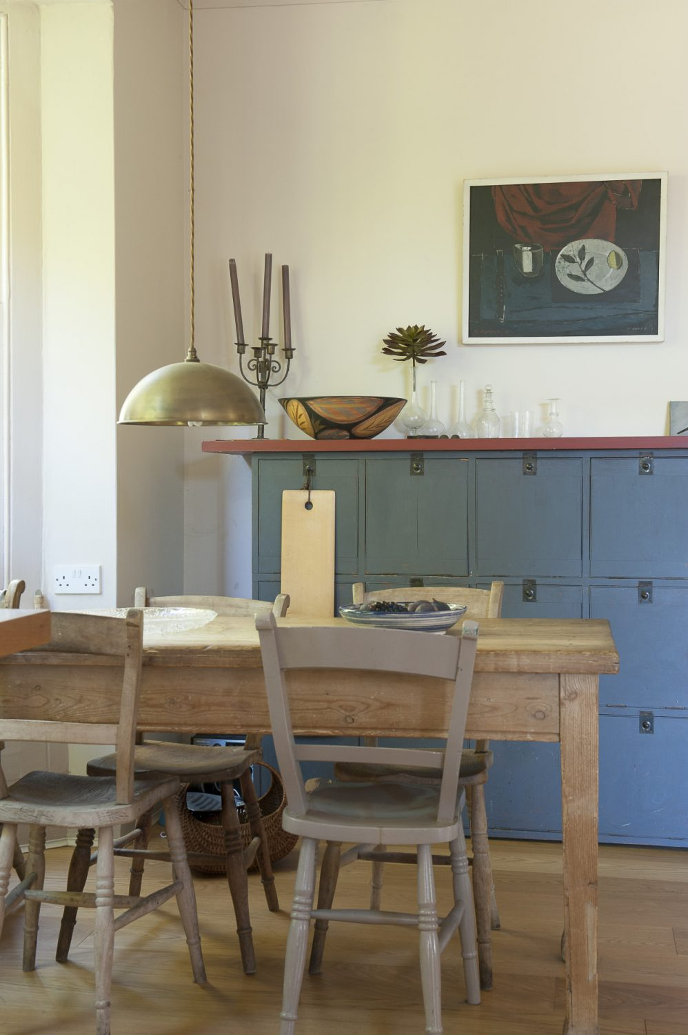A rustic stripped-wood table sits in the corner of the large kitchen-cum-dining room, with side cupboards painted in a strong blue to complement the colour of the 'unfitted' kitchen