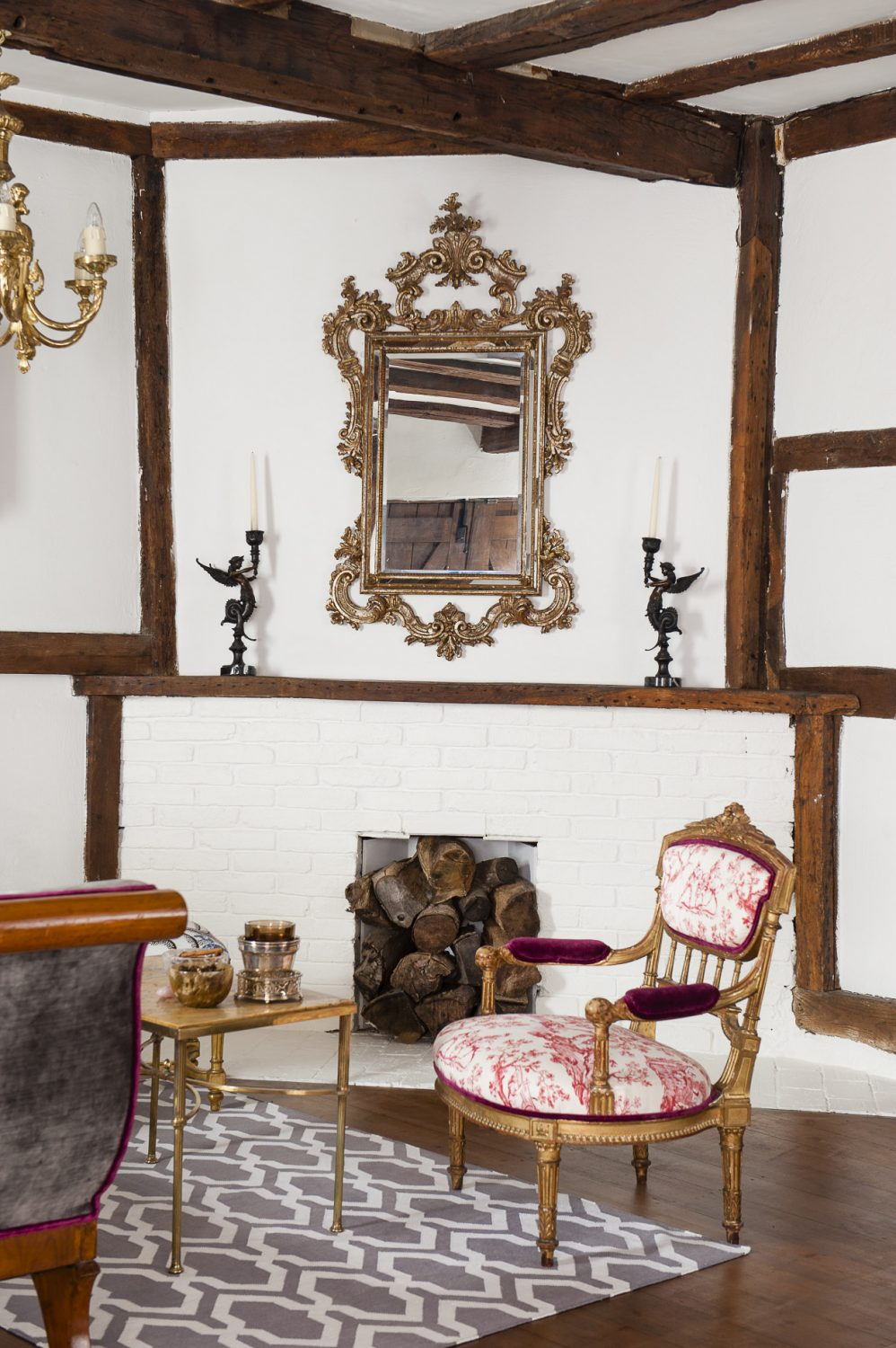 A Venetian rococo mirror is mounted above the painted brickwork of the fireplace