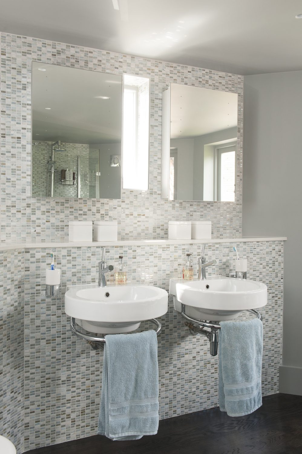 The natural light bounces off the iridescent rectangular tiles covering the wall behind the twin basins