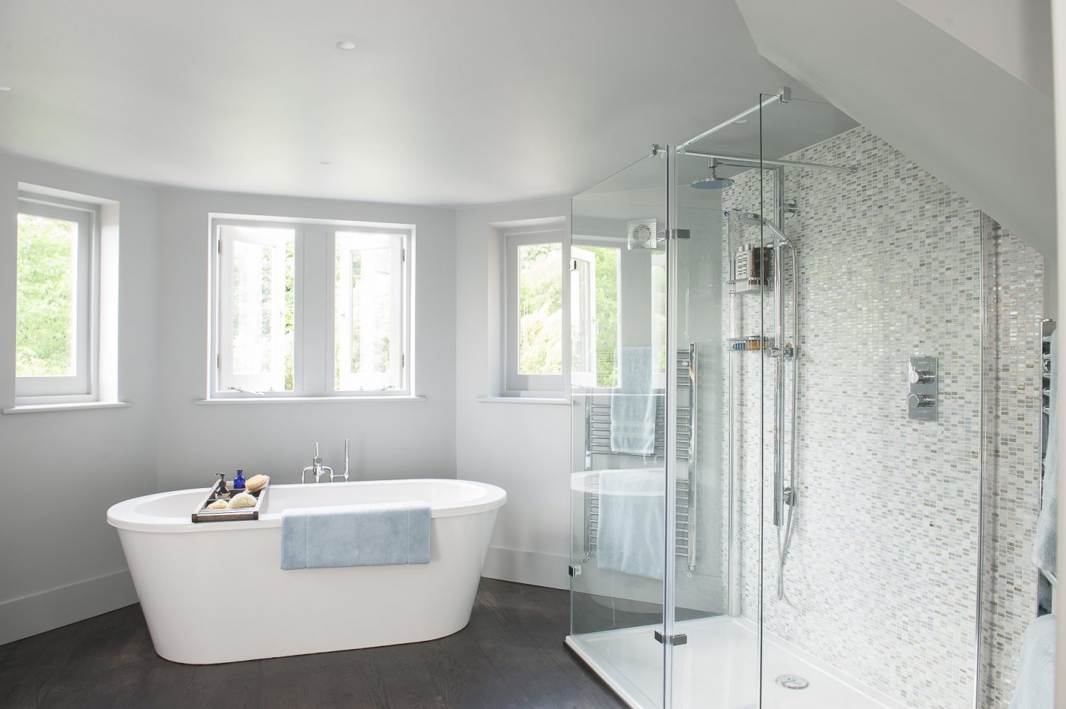 The en suite bathroom in the master suite occupies one of the upper rooms of the octagonal tower, which links the new extension with the original building. Light pours in through four windows
