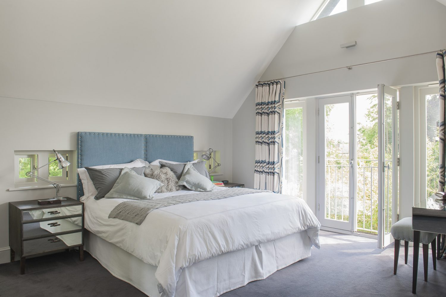 The master bedroom is flooded with light from a vaulted ceiling and French windows onto a Juliet balcony, further enhanced by Jane's choice of pale grey for the walls, bed linen and the background colour in the Larsen graphic weave fabric of the curtains. The windows on either side of the bed act like extensions of the upholstered headboard, with a pleasing symmetrical effect. The mirrored side tables, specially designed by Nathan for this room, further bounce the light around, as do the chrome bedside lamps which are original vintage Anglepoise