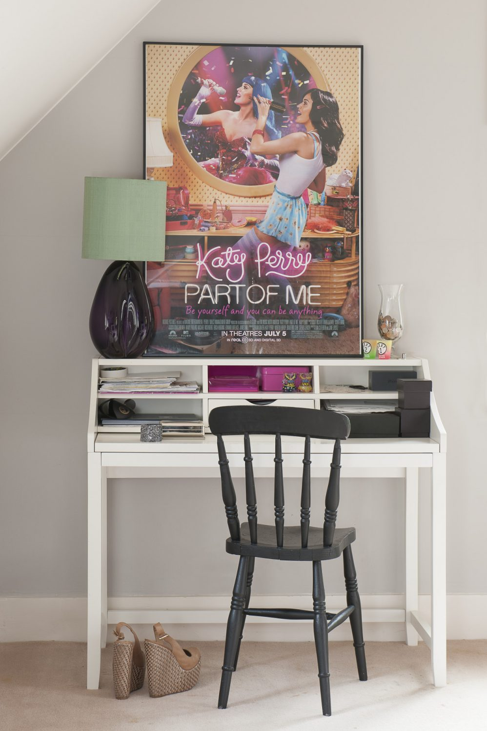 The decorative scheme is continued with the white desk and black chair, with pink accents in the accessories and poster. The lamp is by Porta Romana