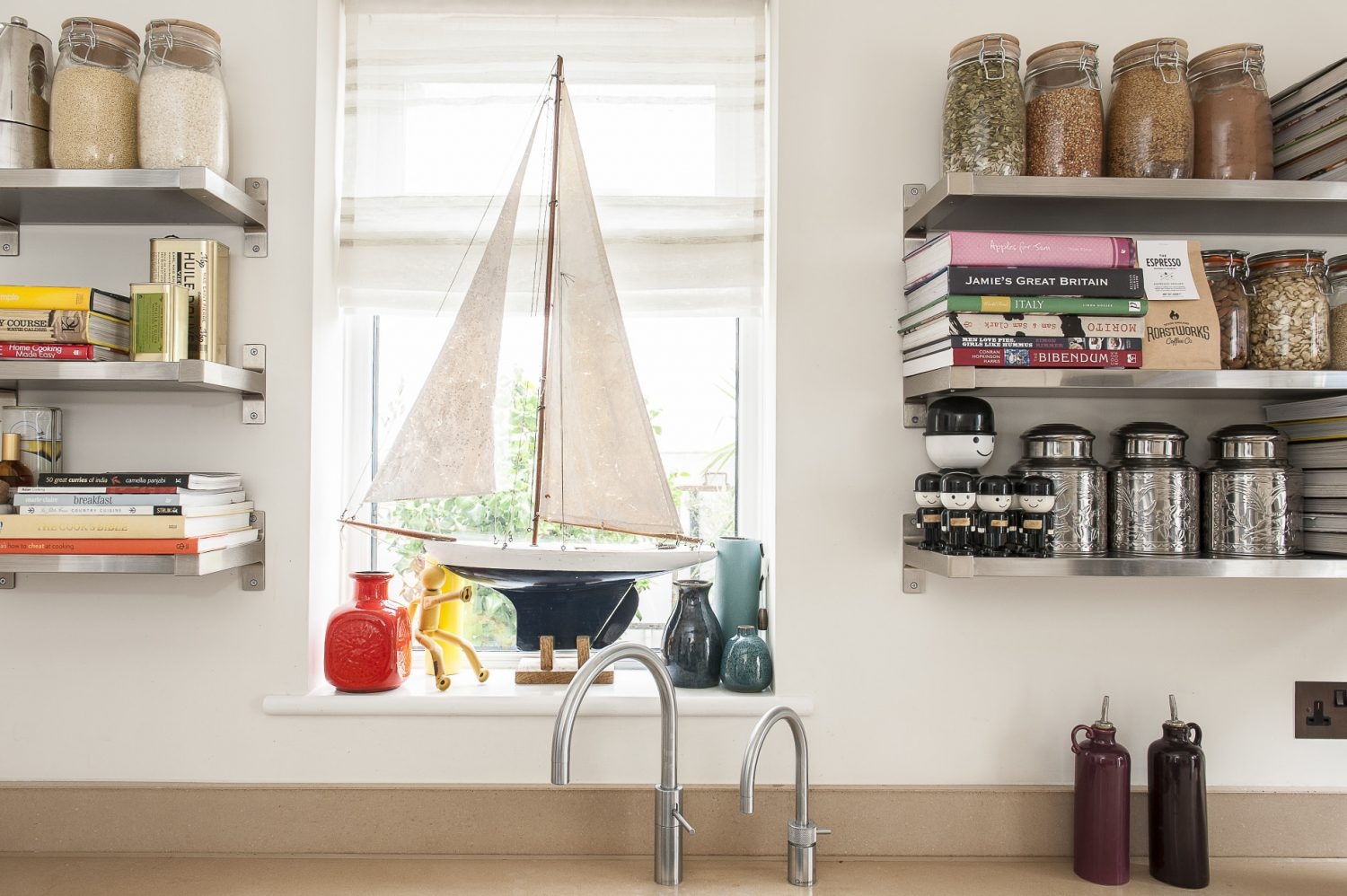 The neutral, simple kitchen units are from Krieder in Tunbridge Wells with open shelving as a design feature in itself and home to colourful ingredients and recipes books, as well as a collection of retro Homepride 'Freds'