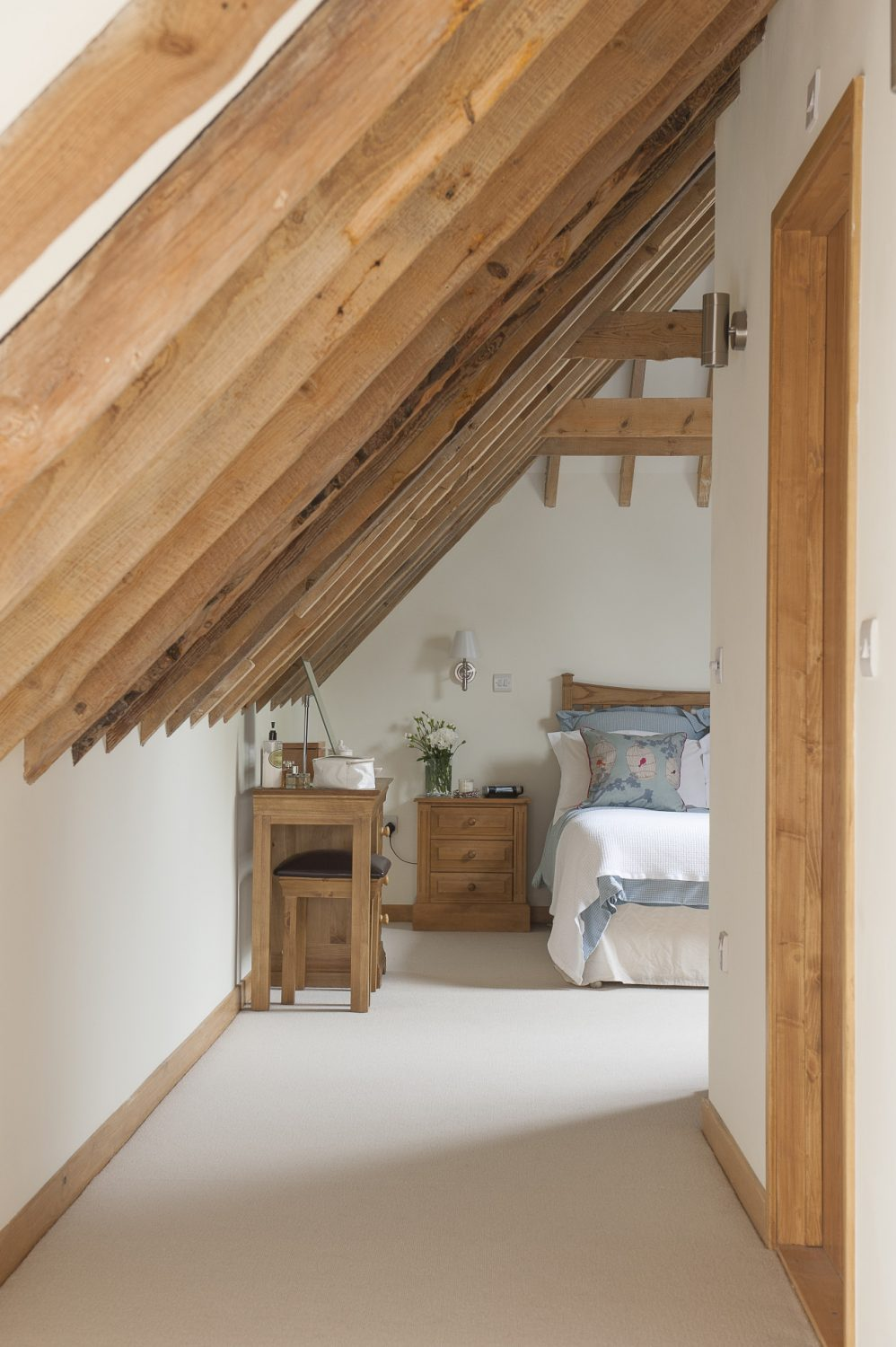 Above, the master bedroom and en suite nestles in the eaves of the building