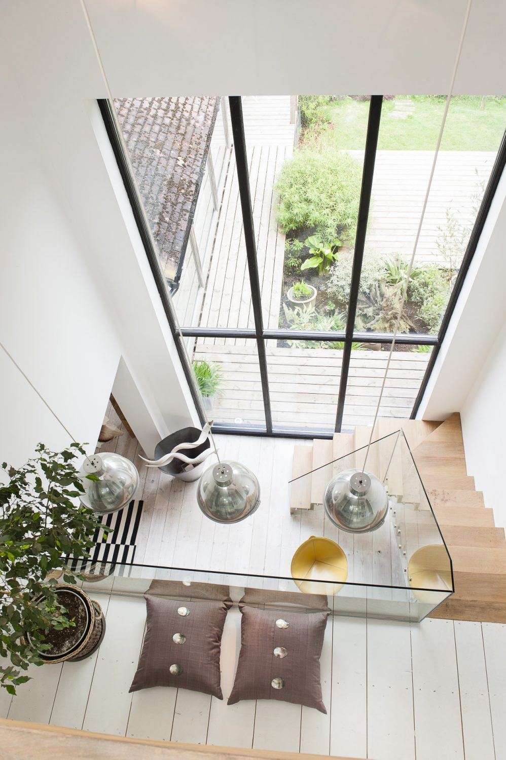A glass banistered gallery looks down over the living space and through a glass wall that extends from the floor to the apex of the roofA glass banistered gallery looks down over the living space and through a glass wall that extends from the floor to the apex of the roof