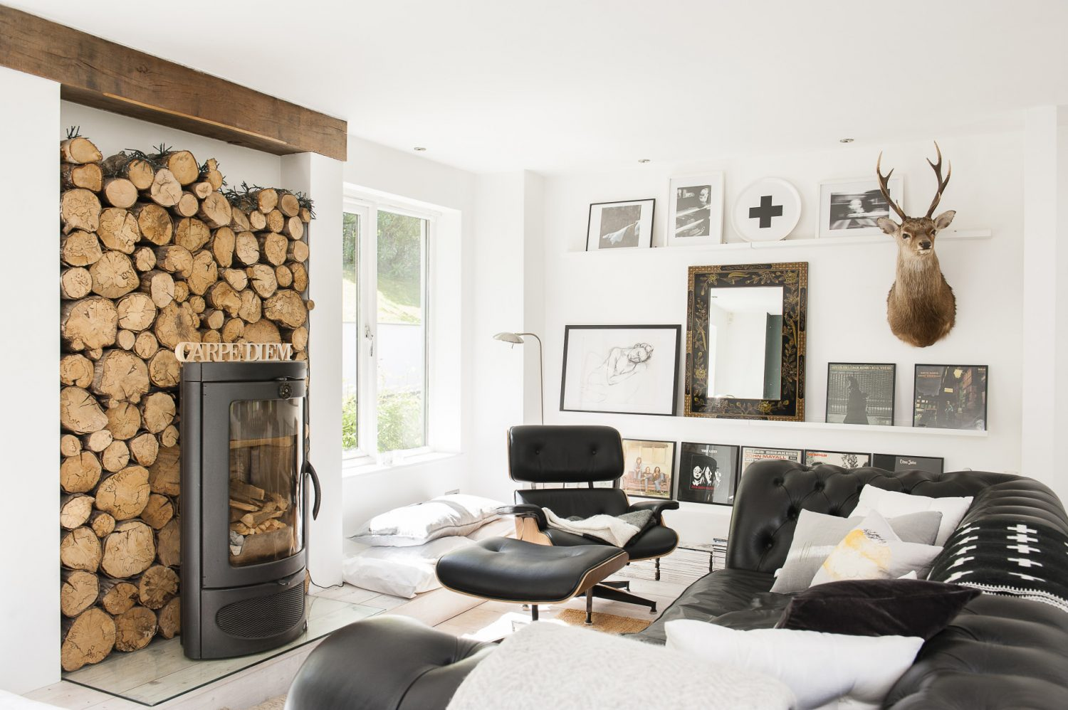 Centrepiece of the snug is an elegant contemporary Austroflamm woodburner backed by a bank of logs. Keeping it company are a Conran four-seater black leather Chesterfield and an Eames recliner. On the wall among the couple's framed classic vinyls is one of Sue's own charcoals.