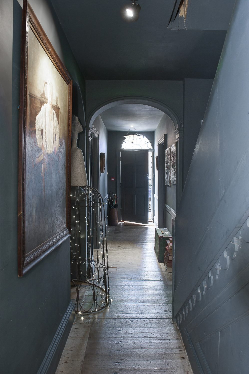 The grey-painted hallway is naturally lit by an original fanlight window above the front door as well as more contemporary fairy lights and spots