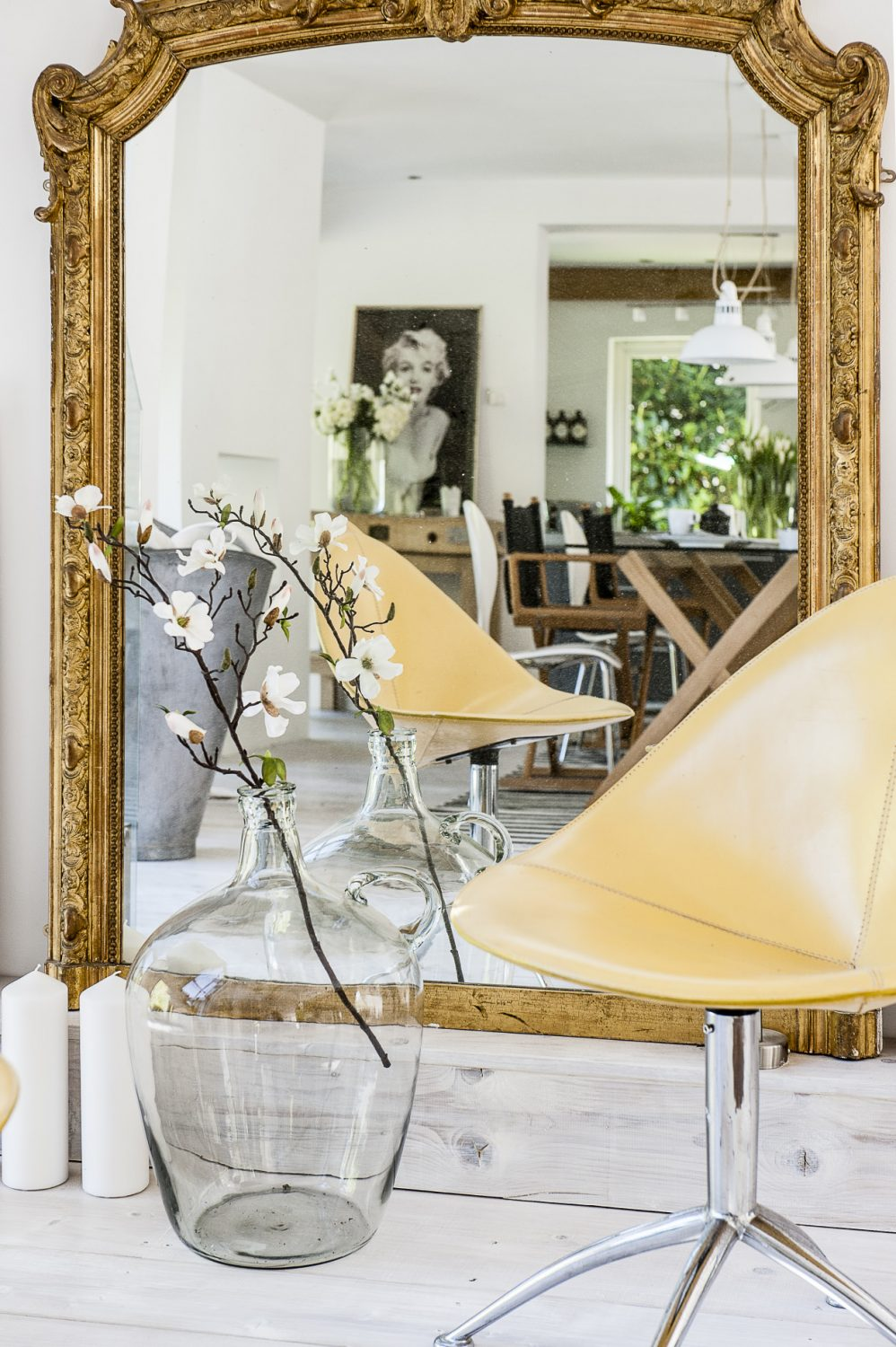 The elegant glass and oak trestle dining table was designed by Sue to seat twelve and is surrounded by a collection of black director's chairs and white Eames chairs