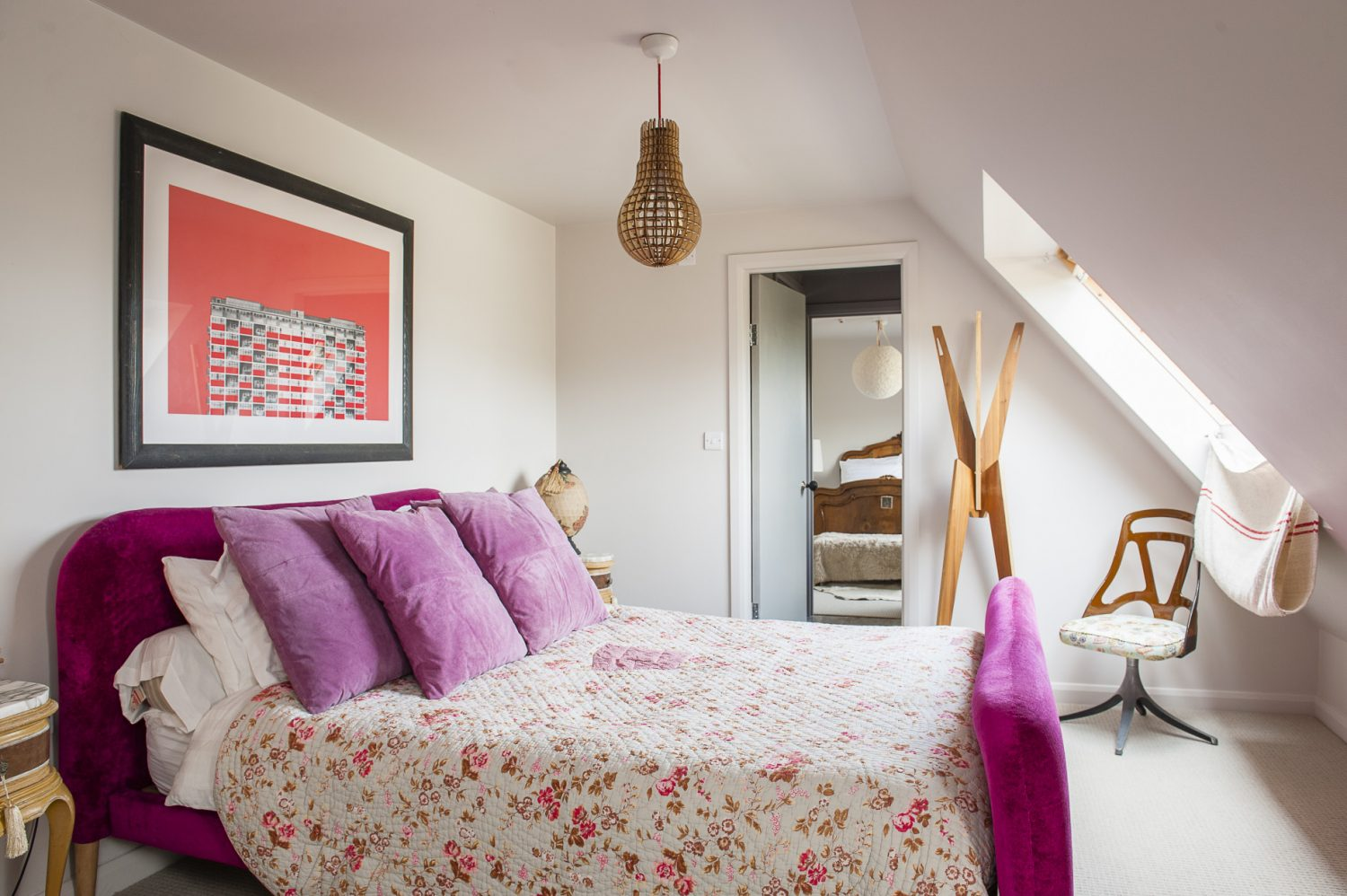 Above the pink velvet bed in the second bedroom is a print of a building in Acton