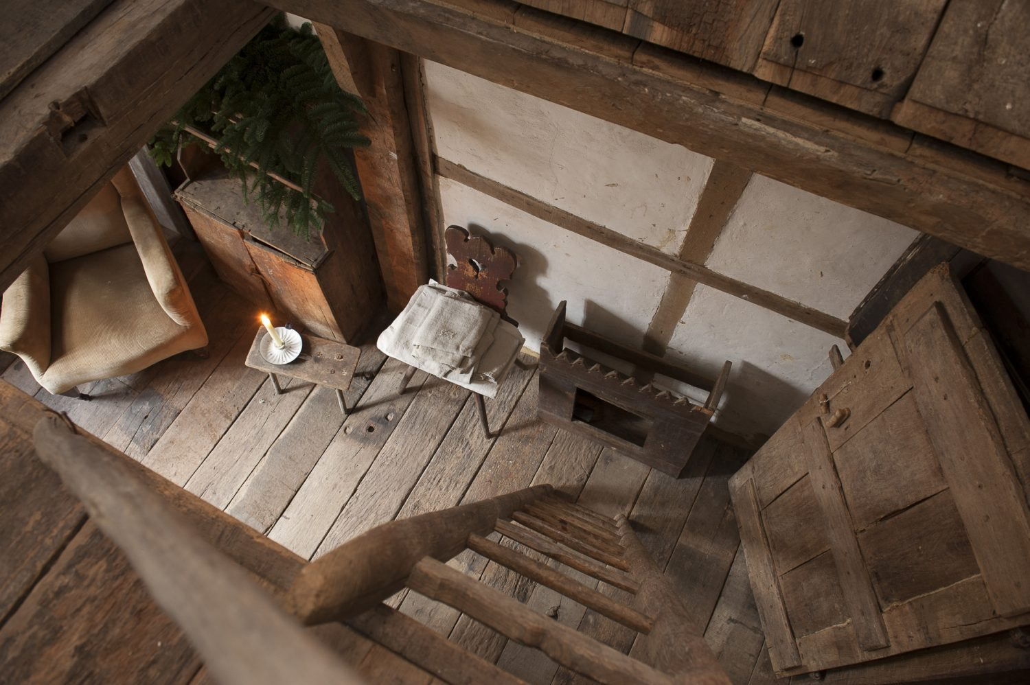 A trap door in the floor of the galleried attic bedroom opens to reveal the room below